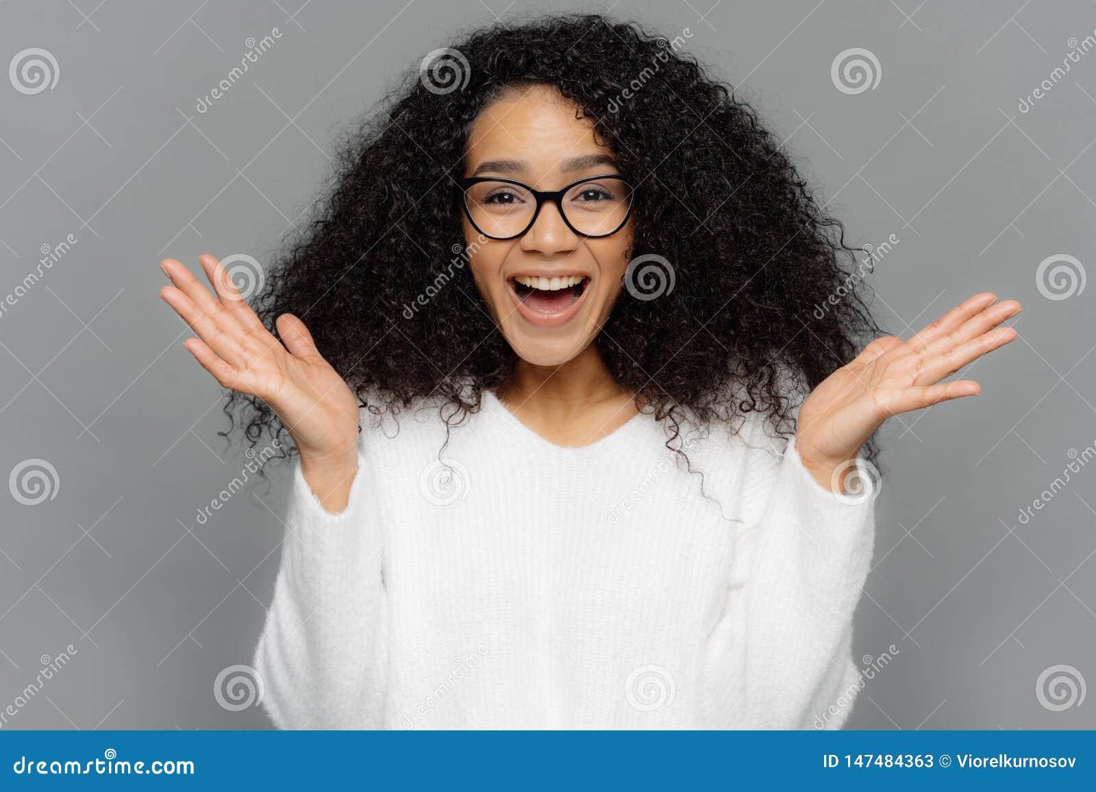Aufrichtiges Gef?hl- und Gef?hlskonzept Optimistisches reizendes junges weibliches verbreitet Hände, Lachen glücklich an sieht an