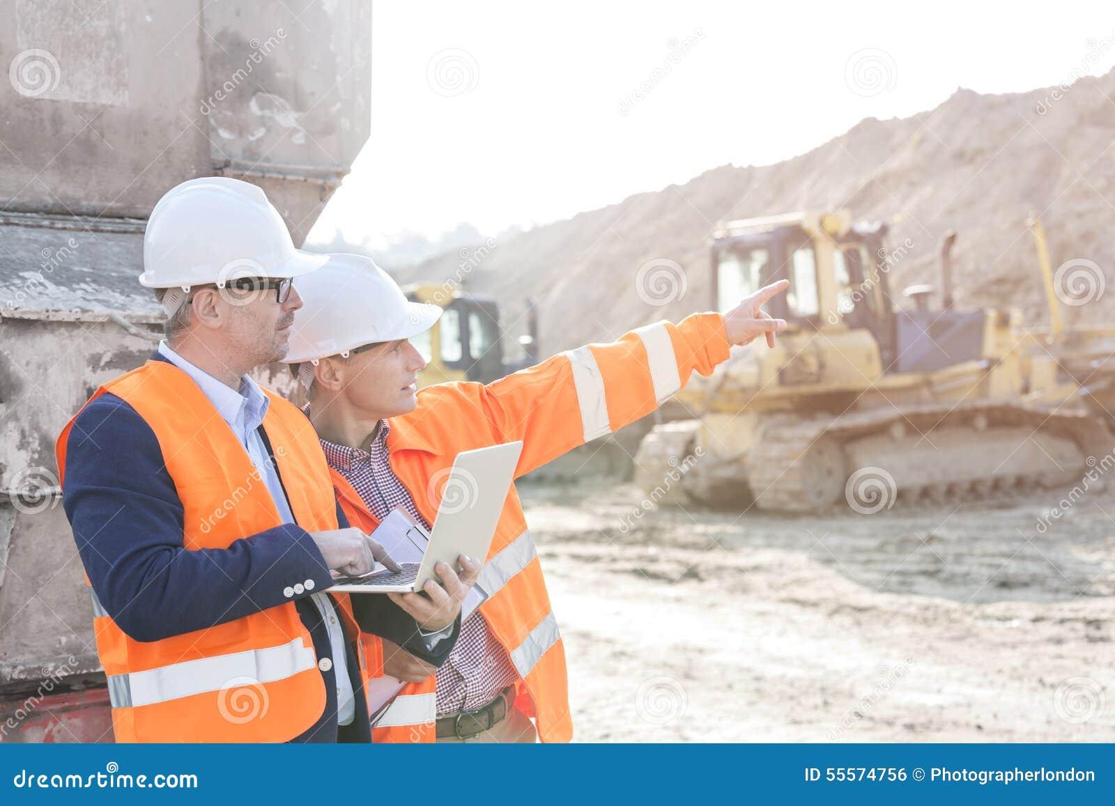 Aufsichtskraft, die dem Mitarbeiter etwas hält Laptop an der Baustelle zeigt