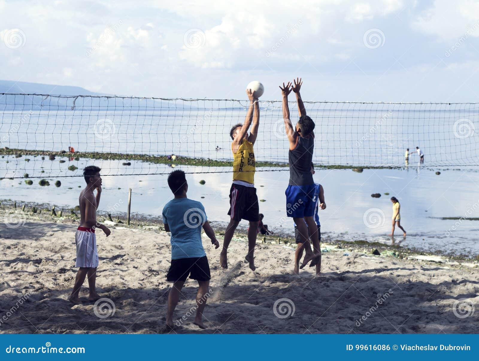 05 2017 Aug, Dumaguete, Filipiny: młode chłopiec bawić się plażową siatkówkę morzem