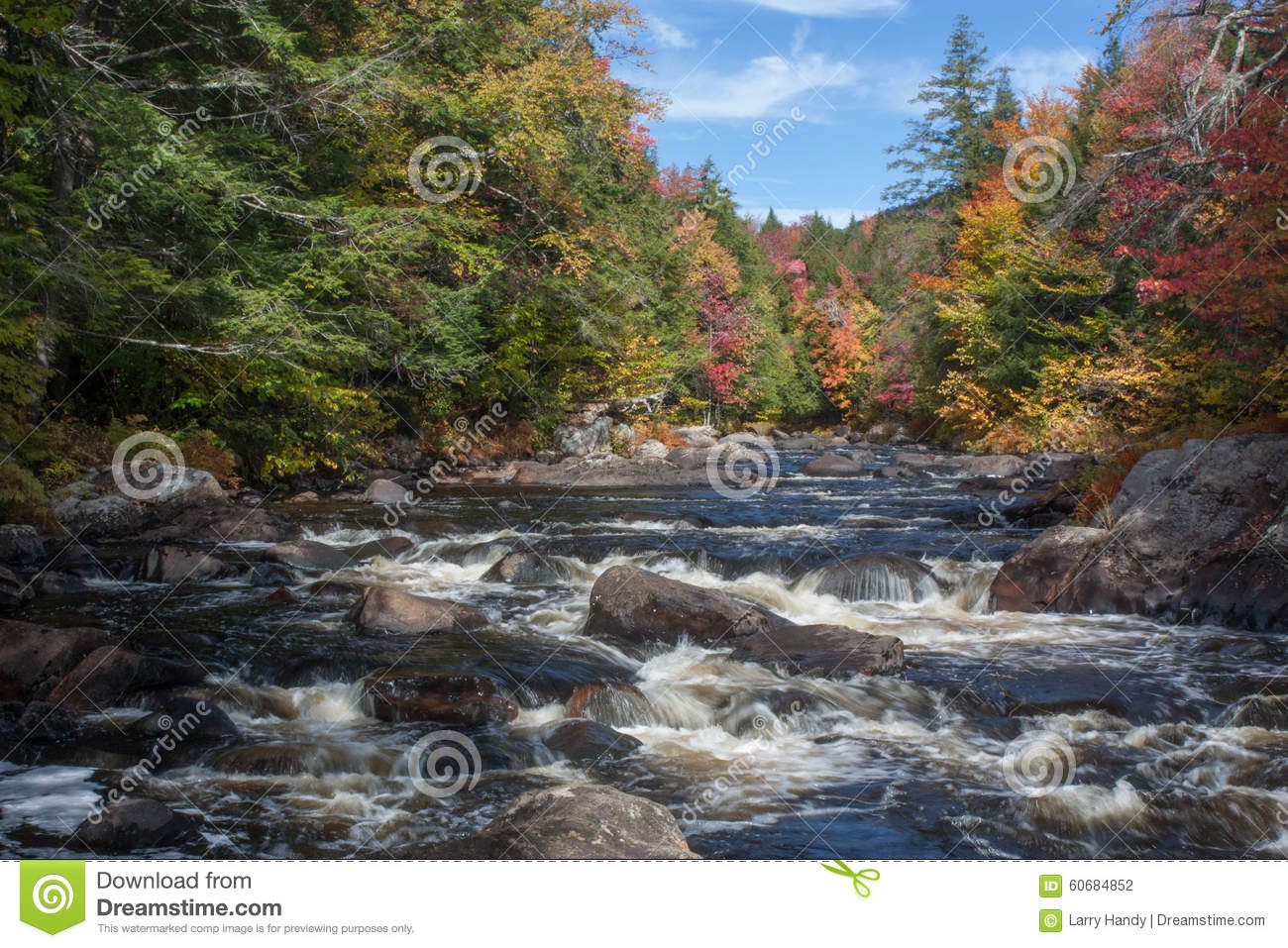 ... stream with rapids in Autumn with blue sky and colorful leaves
