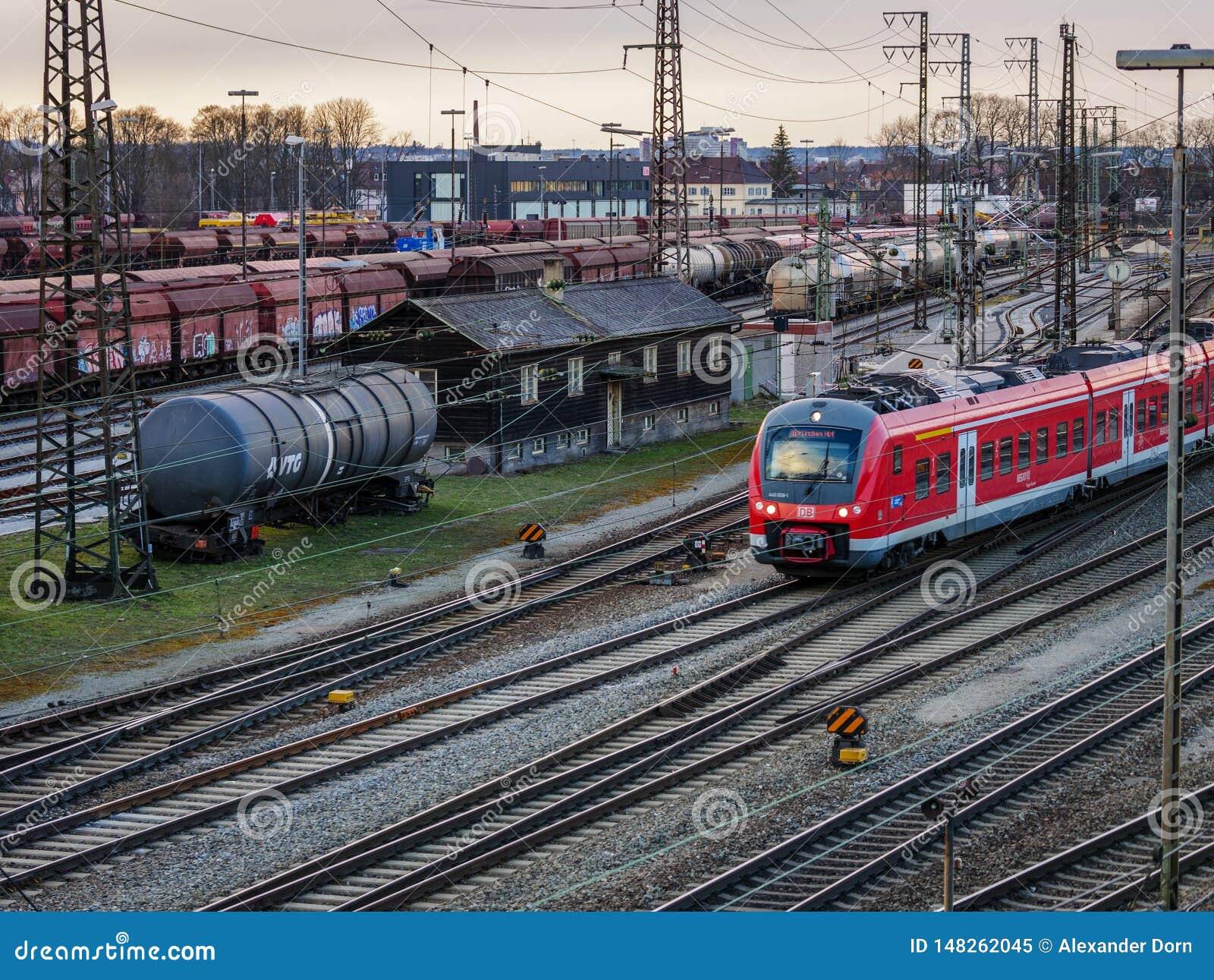 Augsburg, Duitsland - Maart 03, 2018: Rode regionale trein van de Duitse spoorwegdienst Deutsche Bahn op sporen in