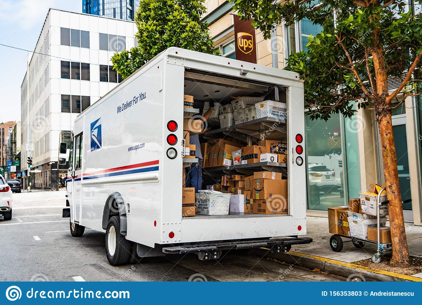 August 10, 2019 San Francisco / CA / USA - USPS delivery van stopped in front of a UPS location, unloading Amazon packages