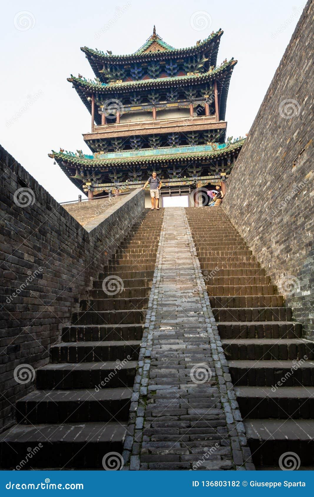 Augustus 2013 - Pingyao, China - Toeristen op de ingangstrap van de oude muren die de Oude stad van Pingyao beschermen