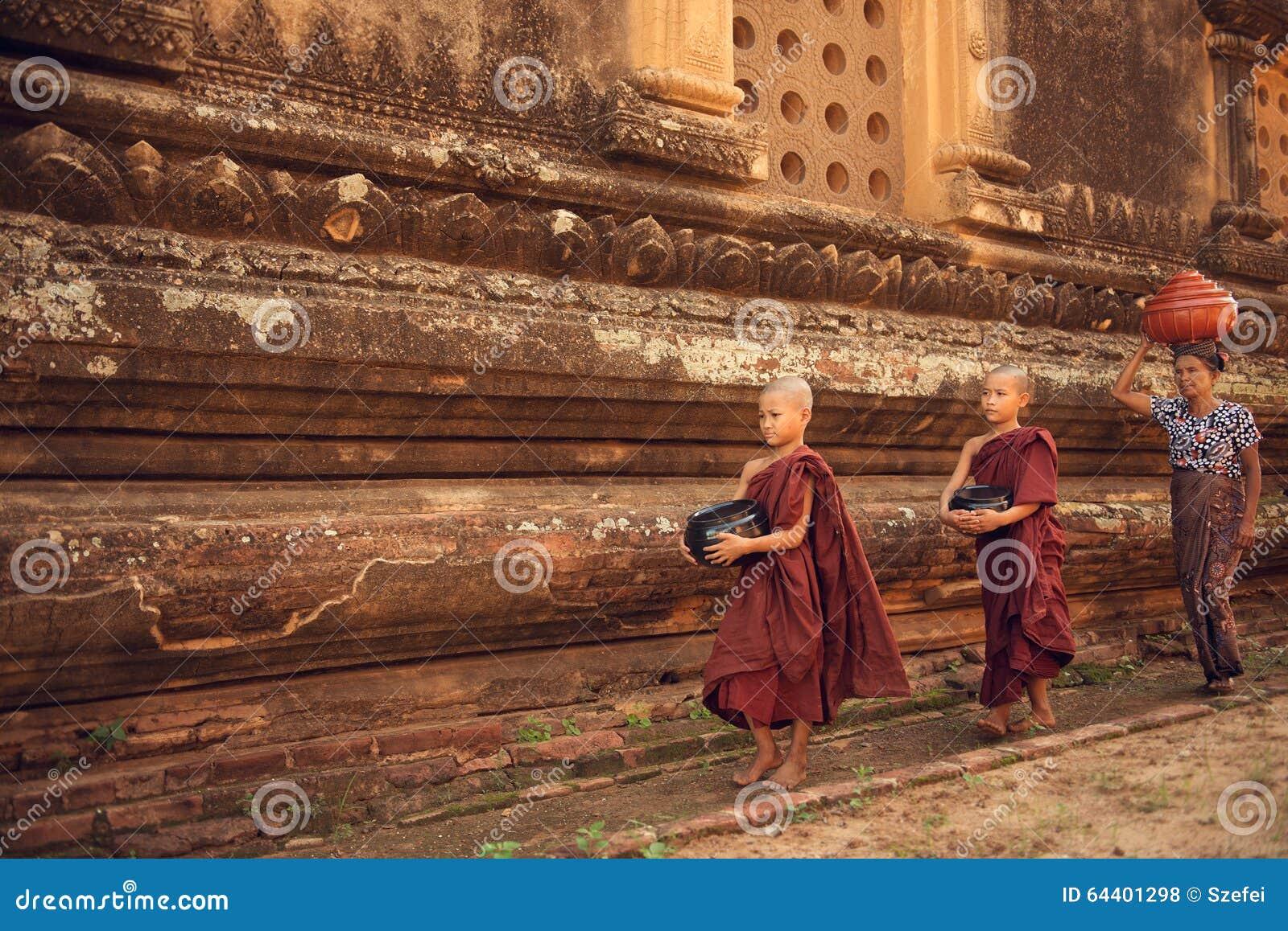 Aumône de marche de moines bouddhistes de novice dans Bagan