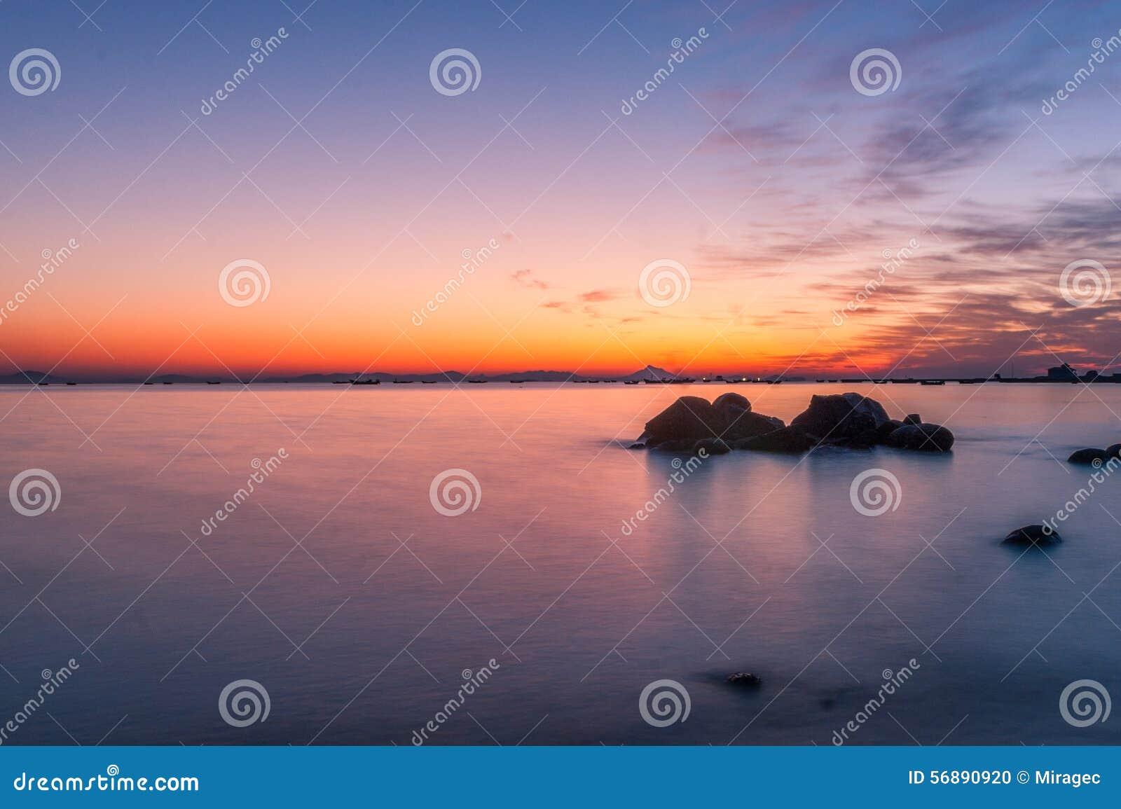 Aumento di Sun alla spiaggia del mare della roccia