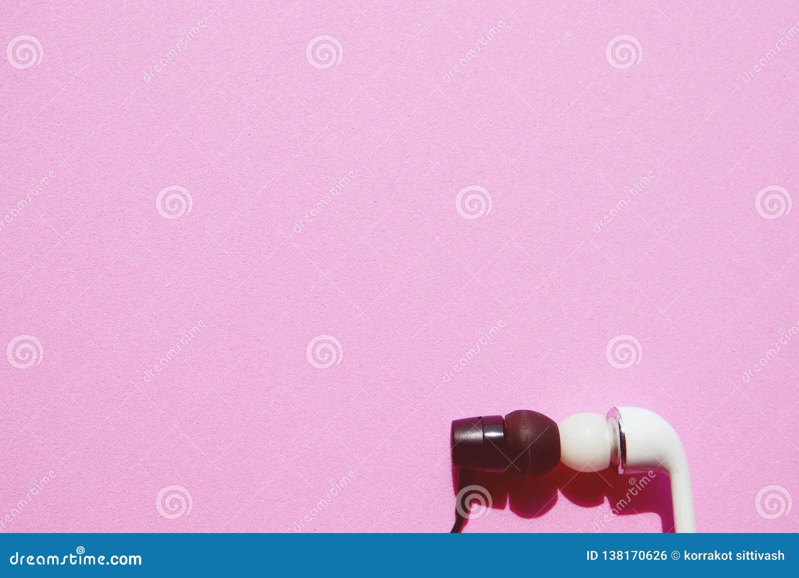 Auriculares blancos y negros que se besan en fondo rosado