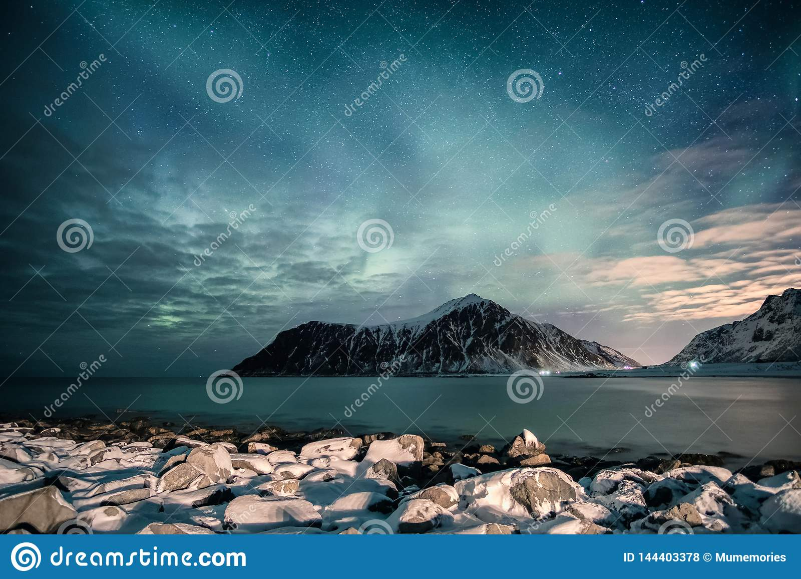 Aurora borealis avec des étoiles sur la gamme de montagne avec le littoral neigeux à la plage de Skagsanden