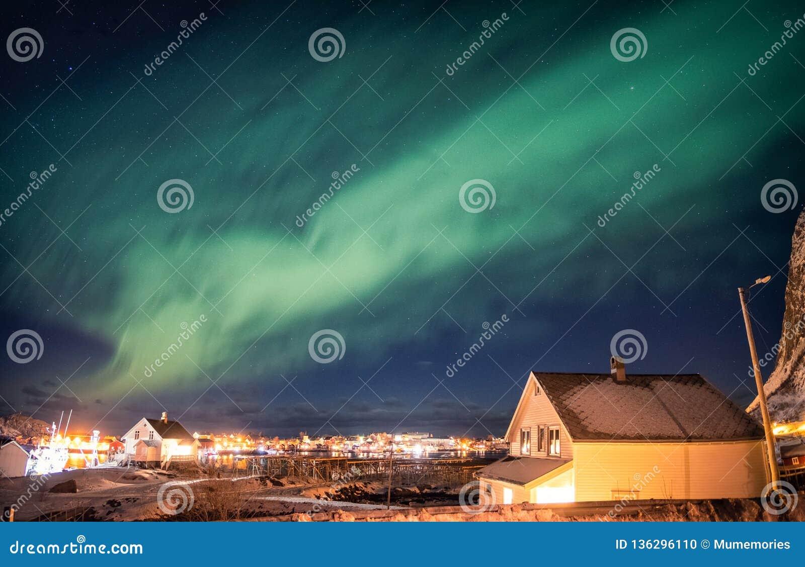 Aurora borealis die over Skandinavisch dorp dansen
