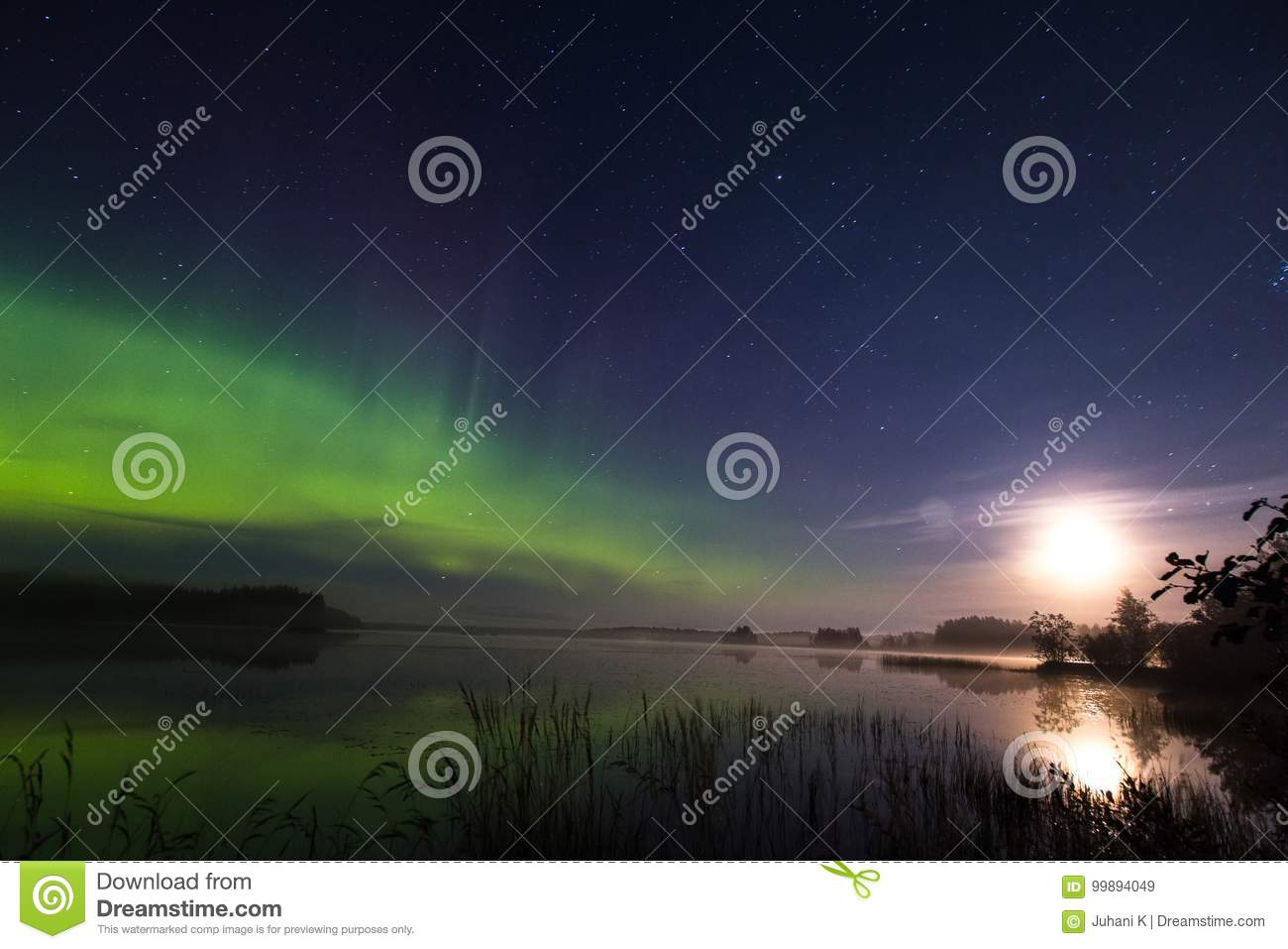 Aurora borealis and full moon above lake in Finland