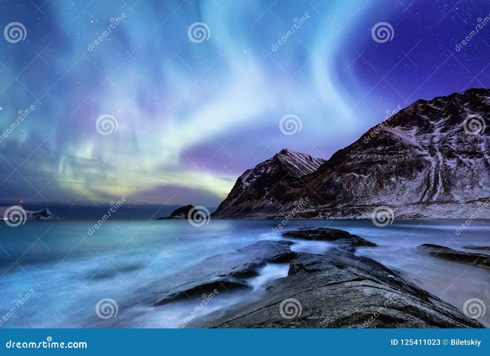 Aurora borealis on the Lofoten islands, Norway. Green northern lights above mountains. Night sky with polar lights.