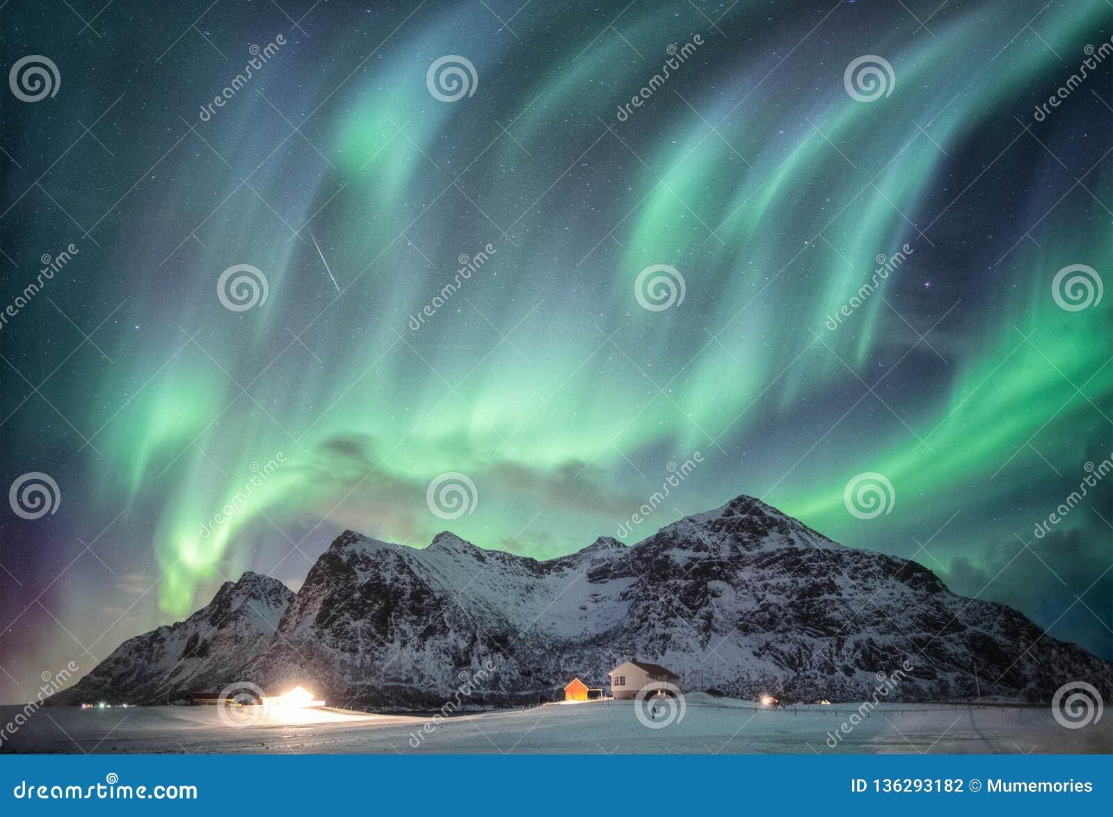 Aurora borealis met sterrig over sneeuwbergketen met verlichtingshuis in Flakstad, Lofoten-eilanden, Noorwegen