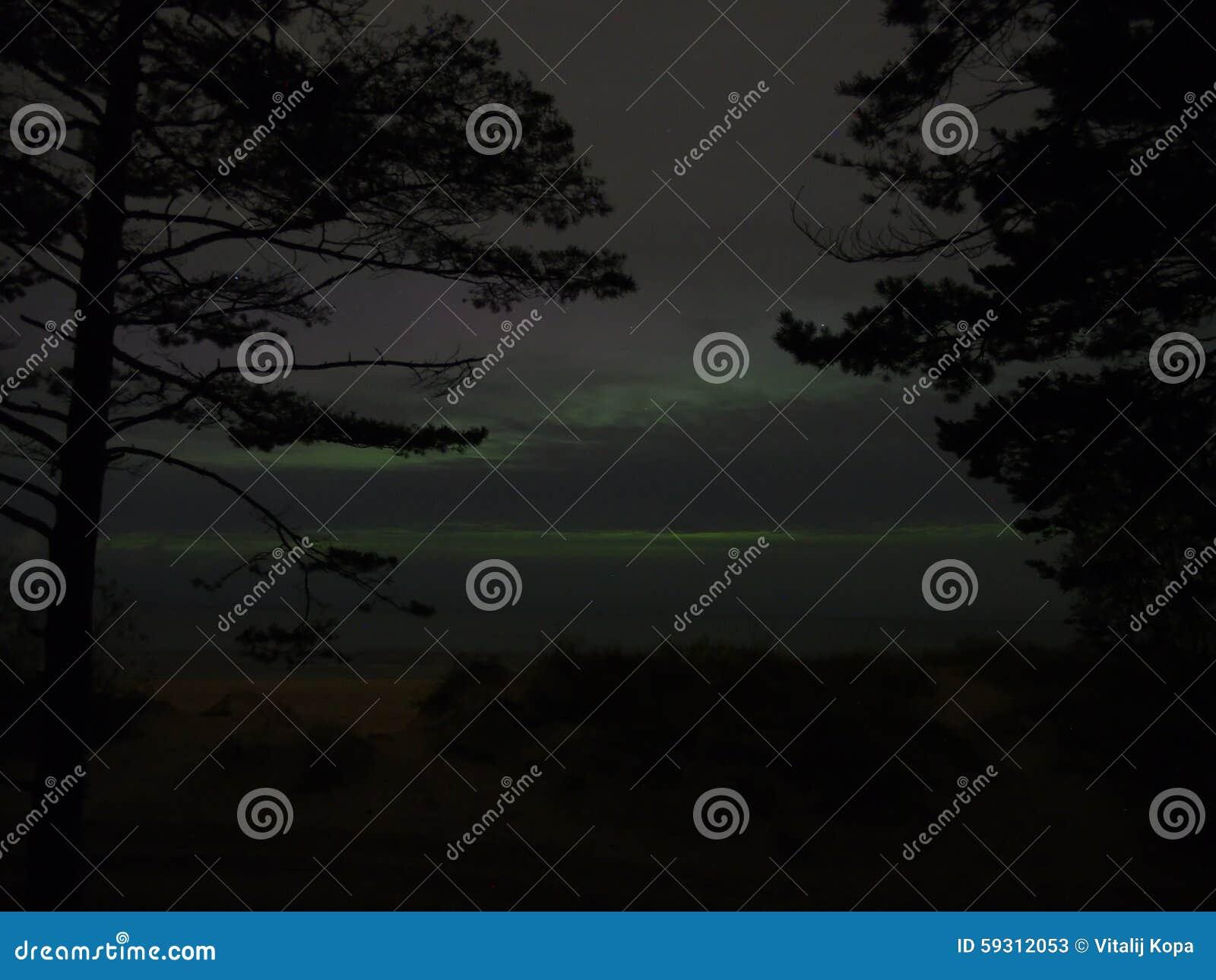 Aurora polar lights and clouds over sea