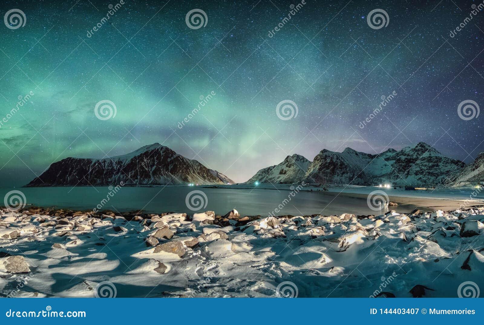 Aurora borealis z gwiazdami nad pasmem górskim z śnieżną linią brzegową przy Skagsanden plażą