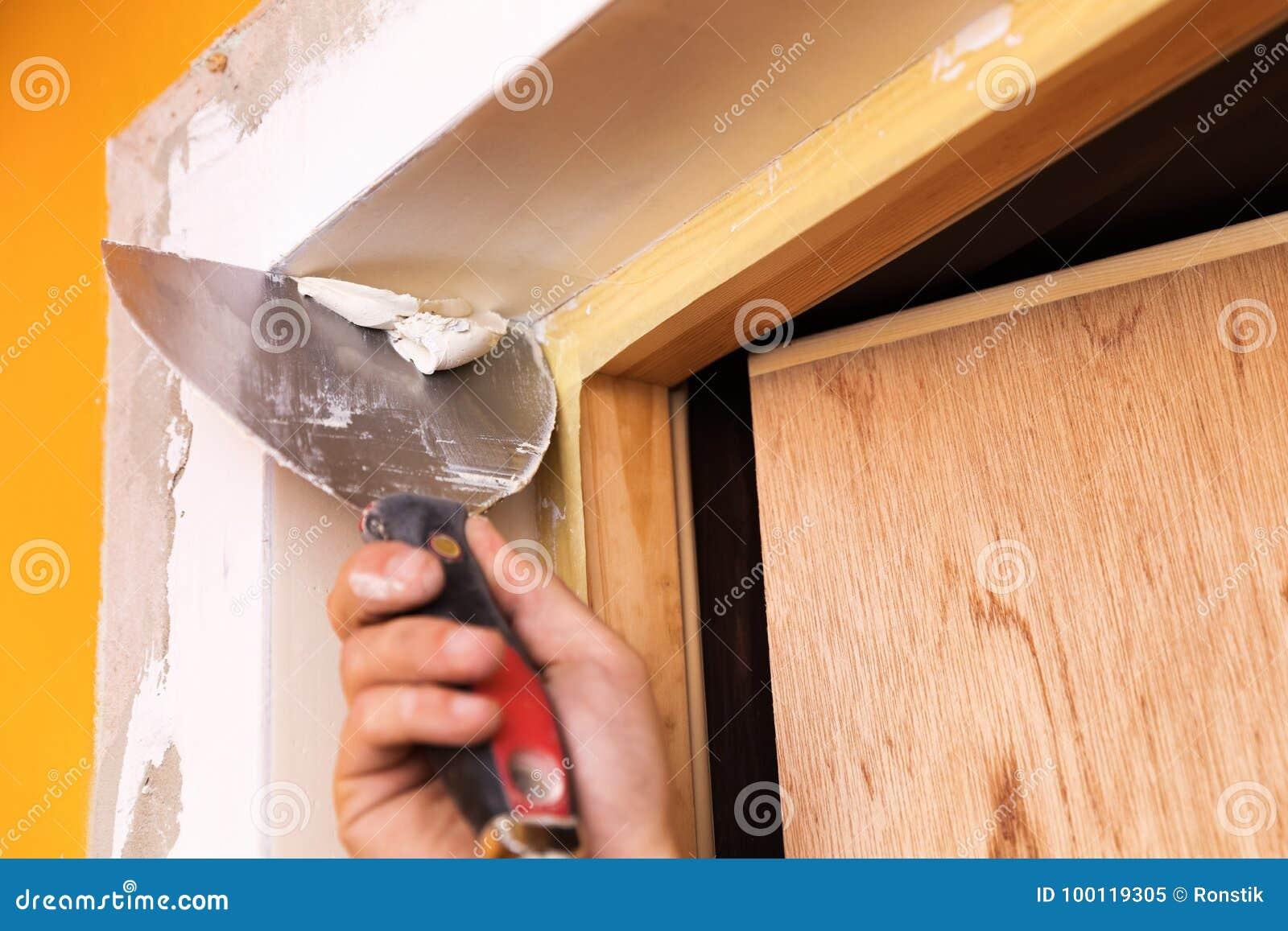 Ausbessernder Gips um eine neue Tür mit Spachtel