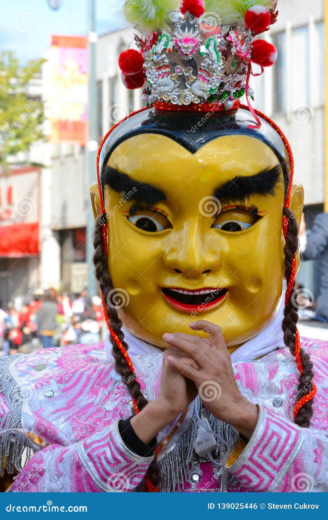 Ausführender in der Maske und Kostüm bei goldenen Dragon Parade, das Chinesische Neujahrsfest feiernd