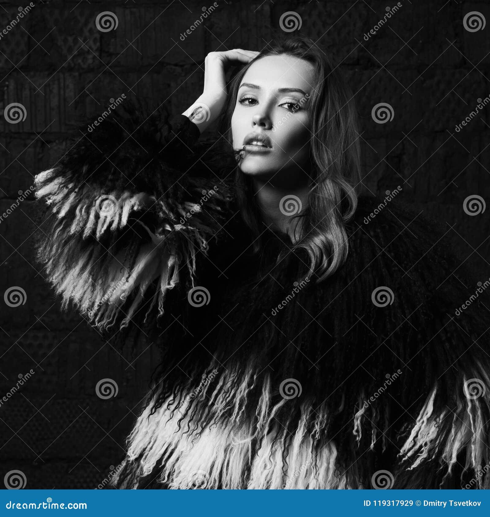 Ausgezeichnete Brunettefrau, die im Fauxpelzmantel am Studio aufwirft