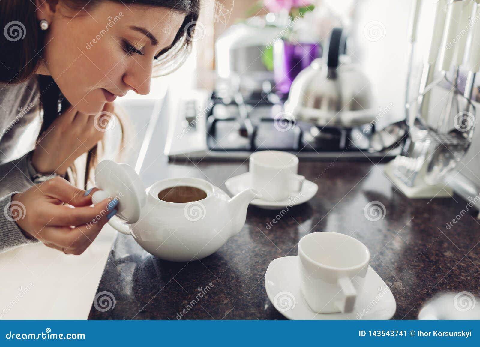 Auslaufender Tee der Frau in keramische Schale bei Tisch