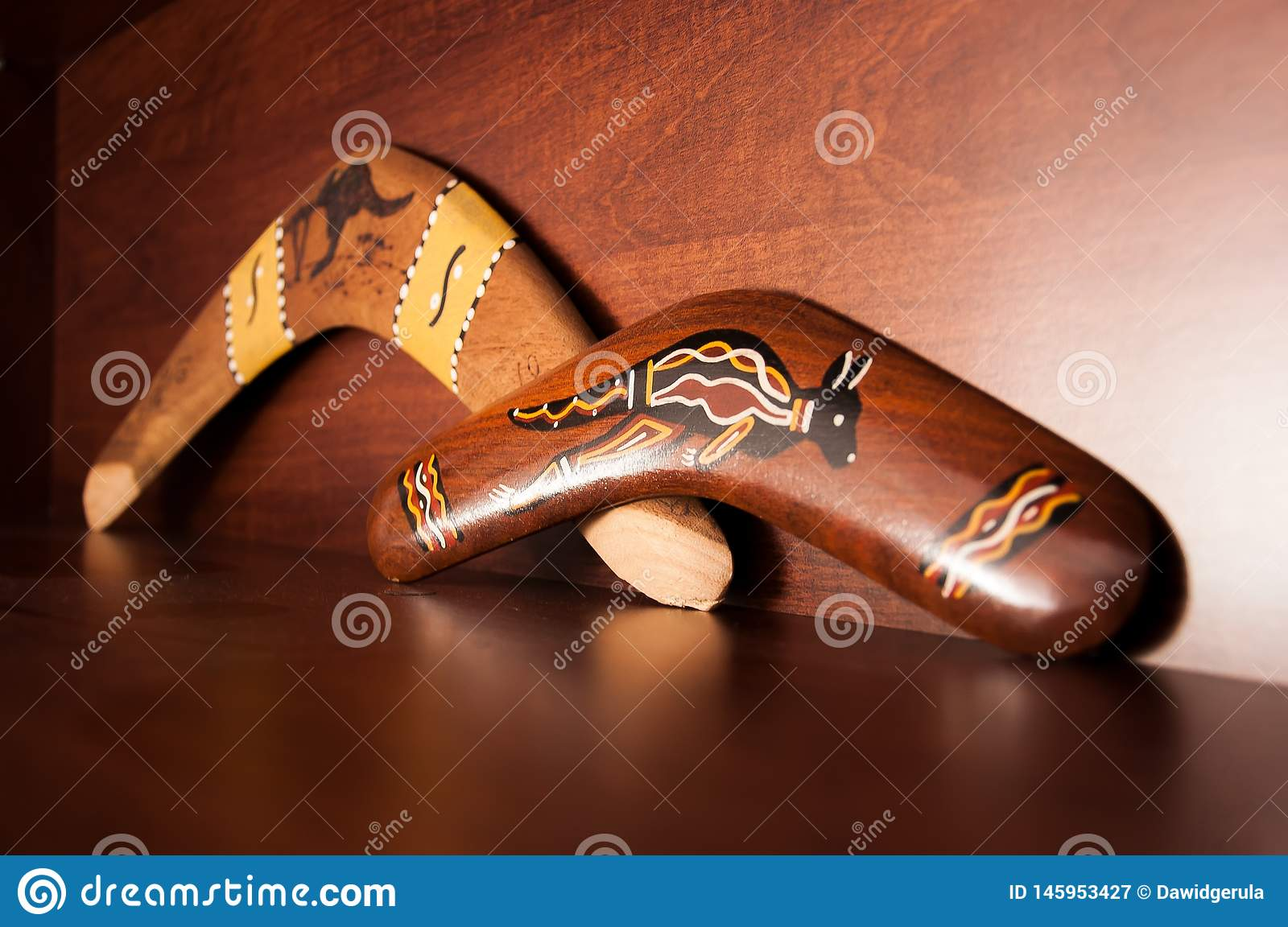 Australian boomerangs seen from the side, lying on the vintage brown shelf. Souvenirs from Australia on display in the living room