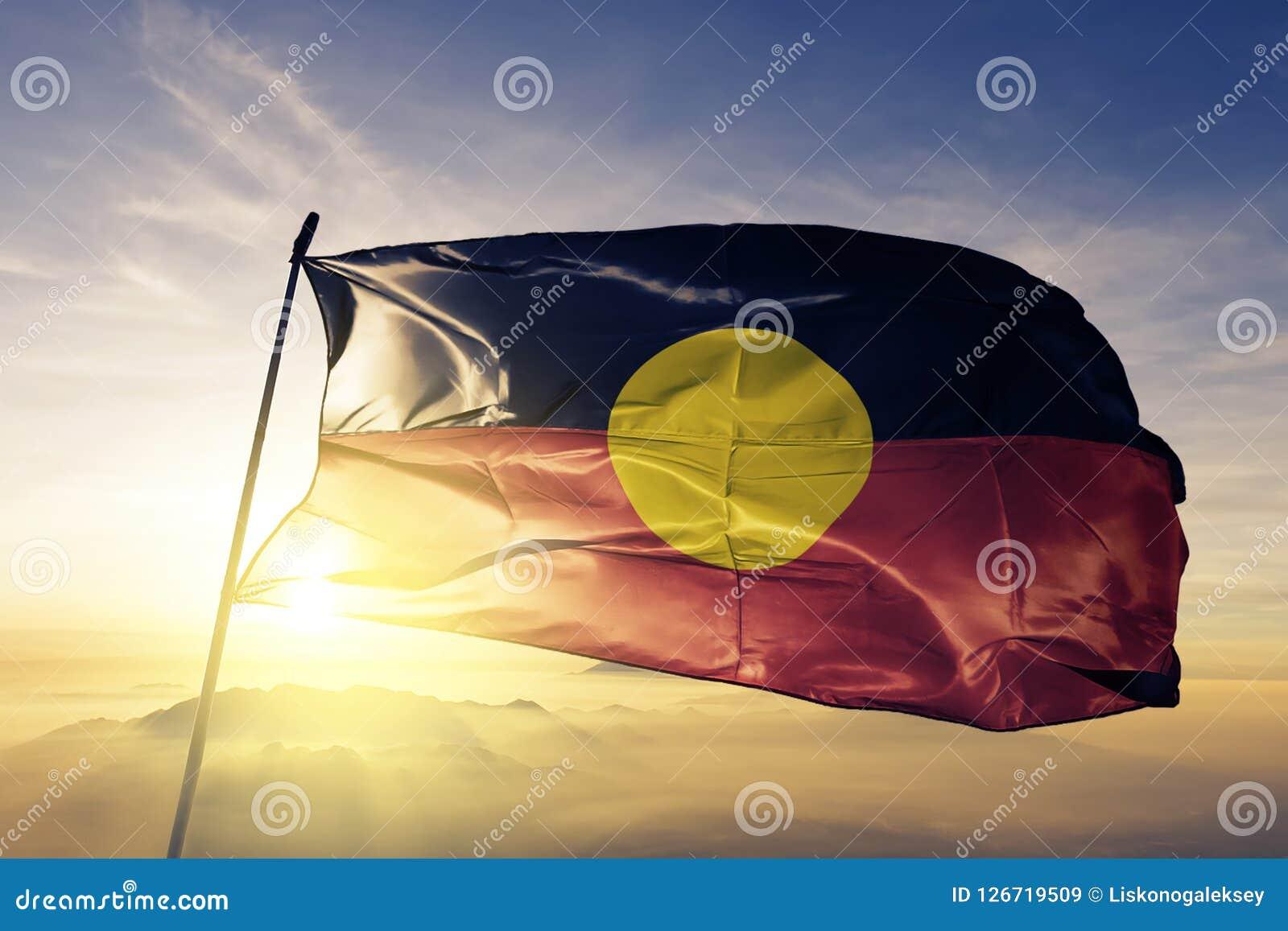 Australijskiej aborygen flaga tkaniny tekstylny sukienny falowanie na odgórnej wschód słońca mgły mgle