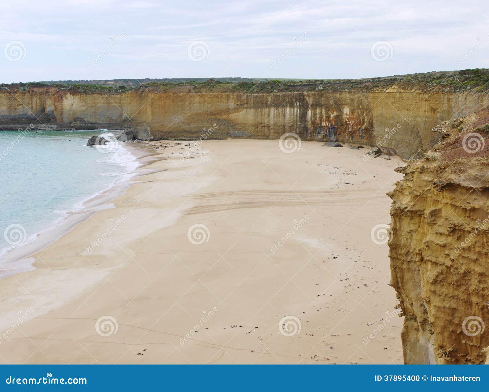 Australisch zandig strand en gele rotsen