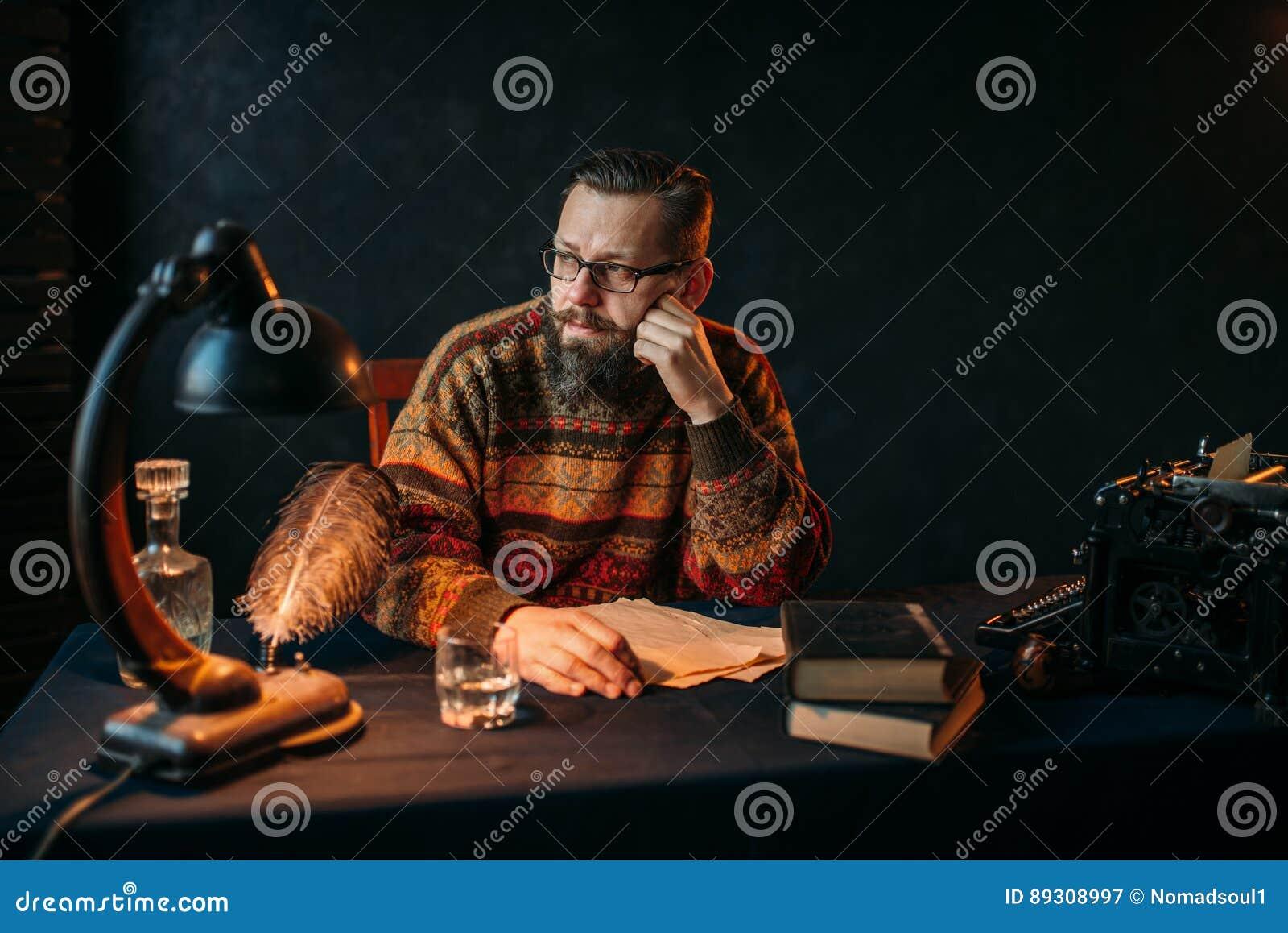 Auteur barbu en verres se reposant à la table