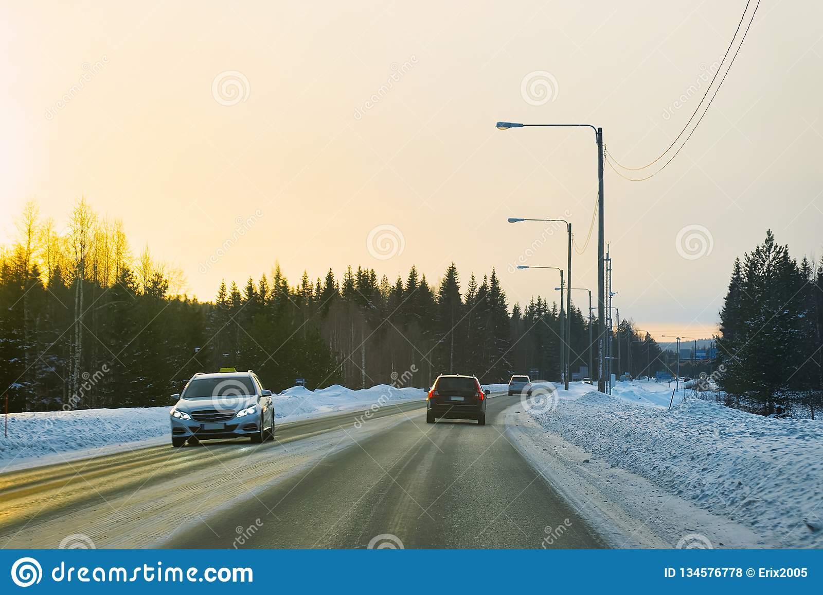 Auto in een weg bij de sneeuwzonsondergang van de winterlapland