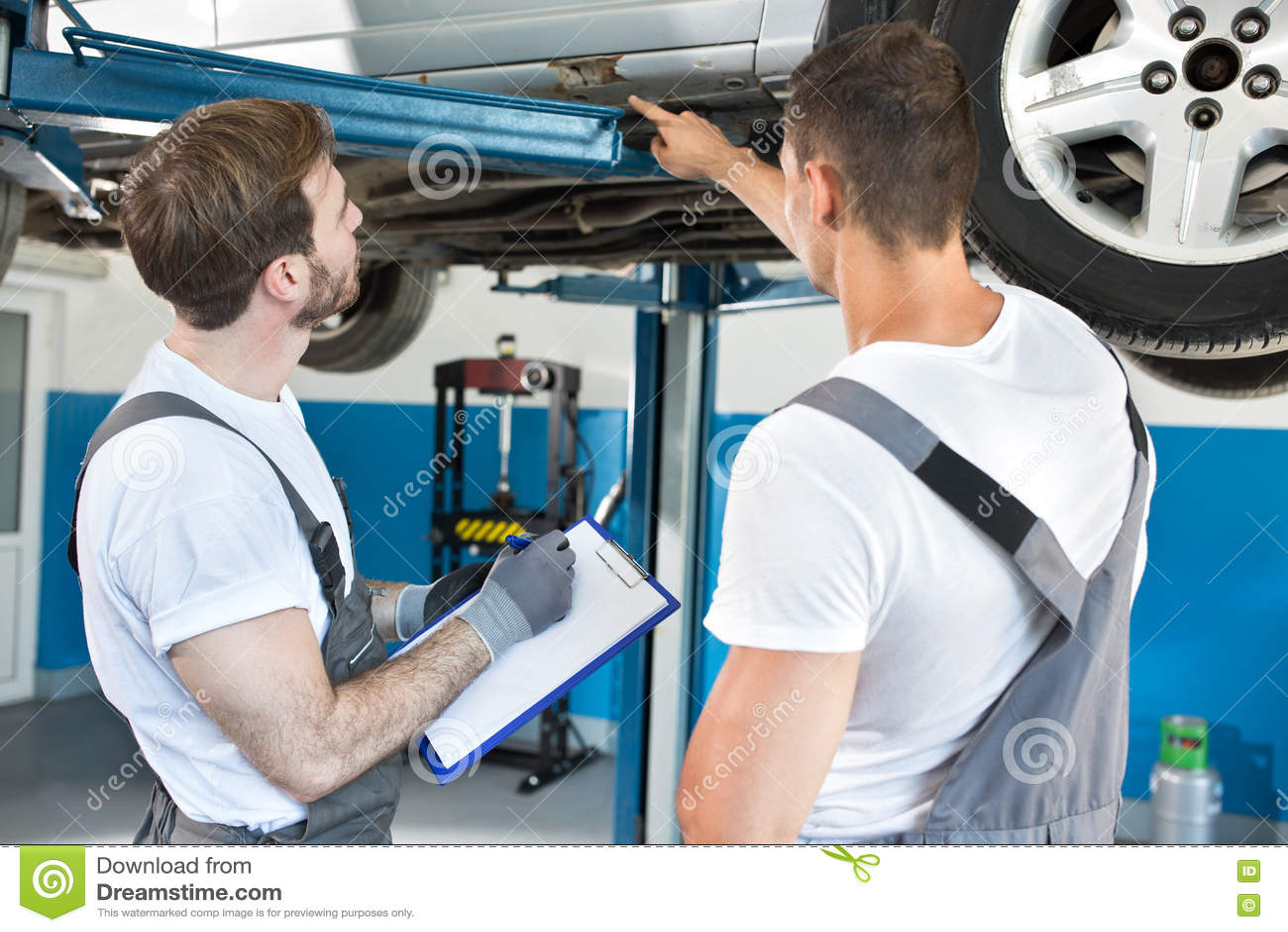 Auto mecânicos da oficina que inspecionam dano ao carro