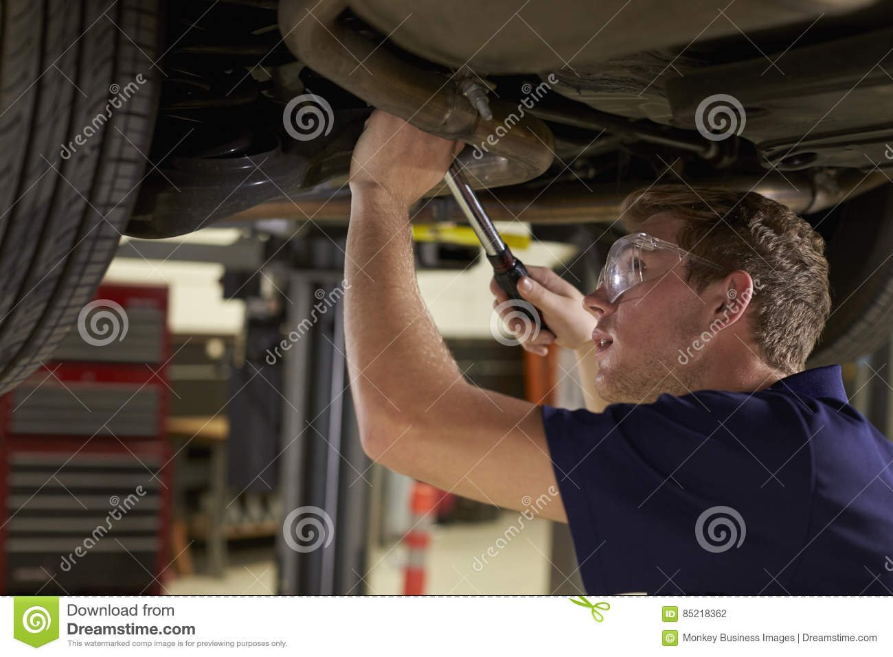 Auto Mechanic Working Underneath Car In Garage