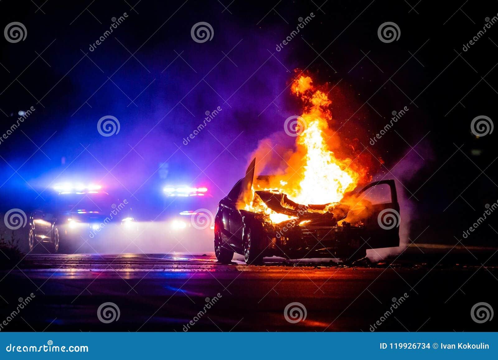 Auto op brand bij nacht met politielichten op achtergrond