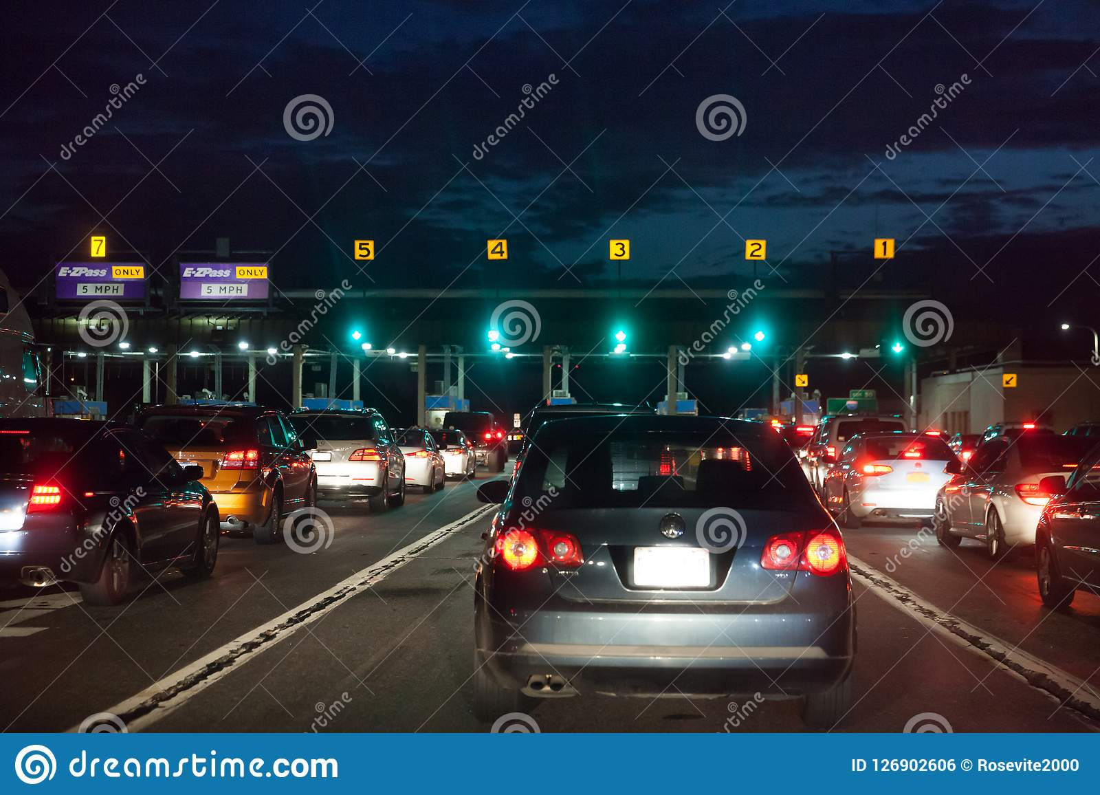 Auto s in een opstelling bij nacht bij de tolpoort om voor tolprijs te betalen