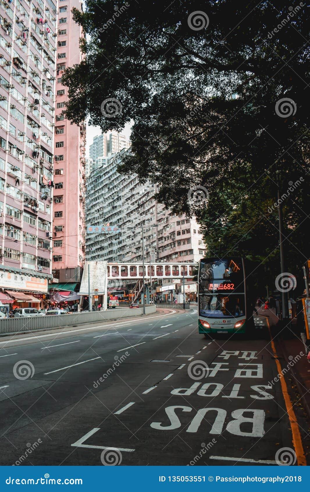 Autobús de dos pisos rojo en una parada de autobús en la parte residencial de Hong Kong