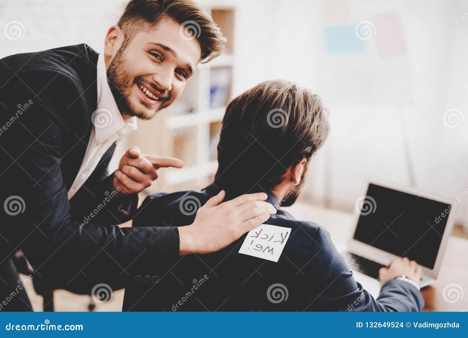Autocollant collé par homme sur le dos du collègue dans le bureau