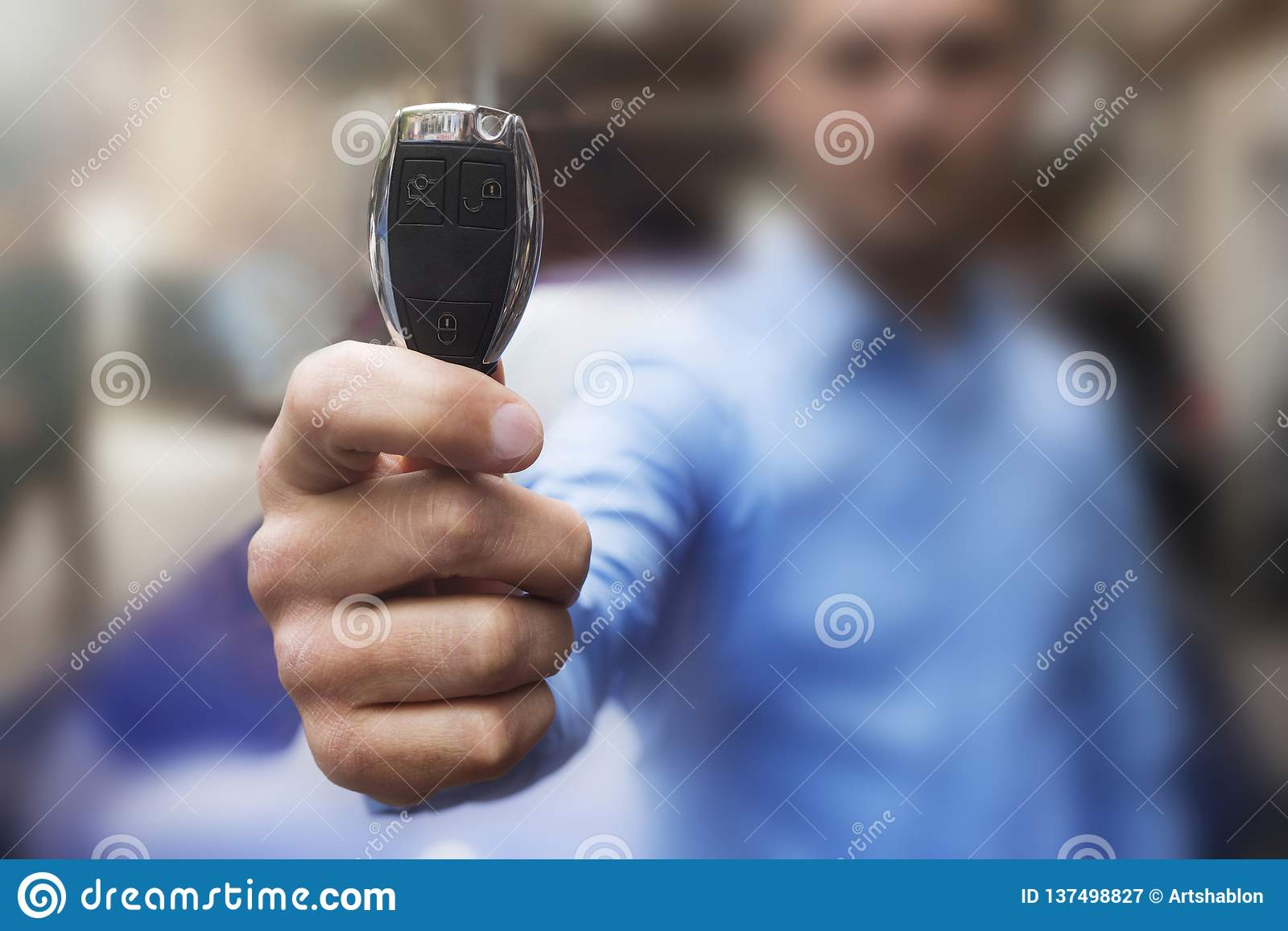 Autohaus- und Mietkonzepthintergrund Die Hand des Mannes stellt die Schlüssel dar