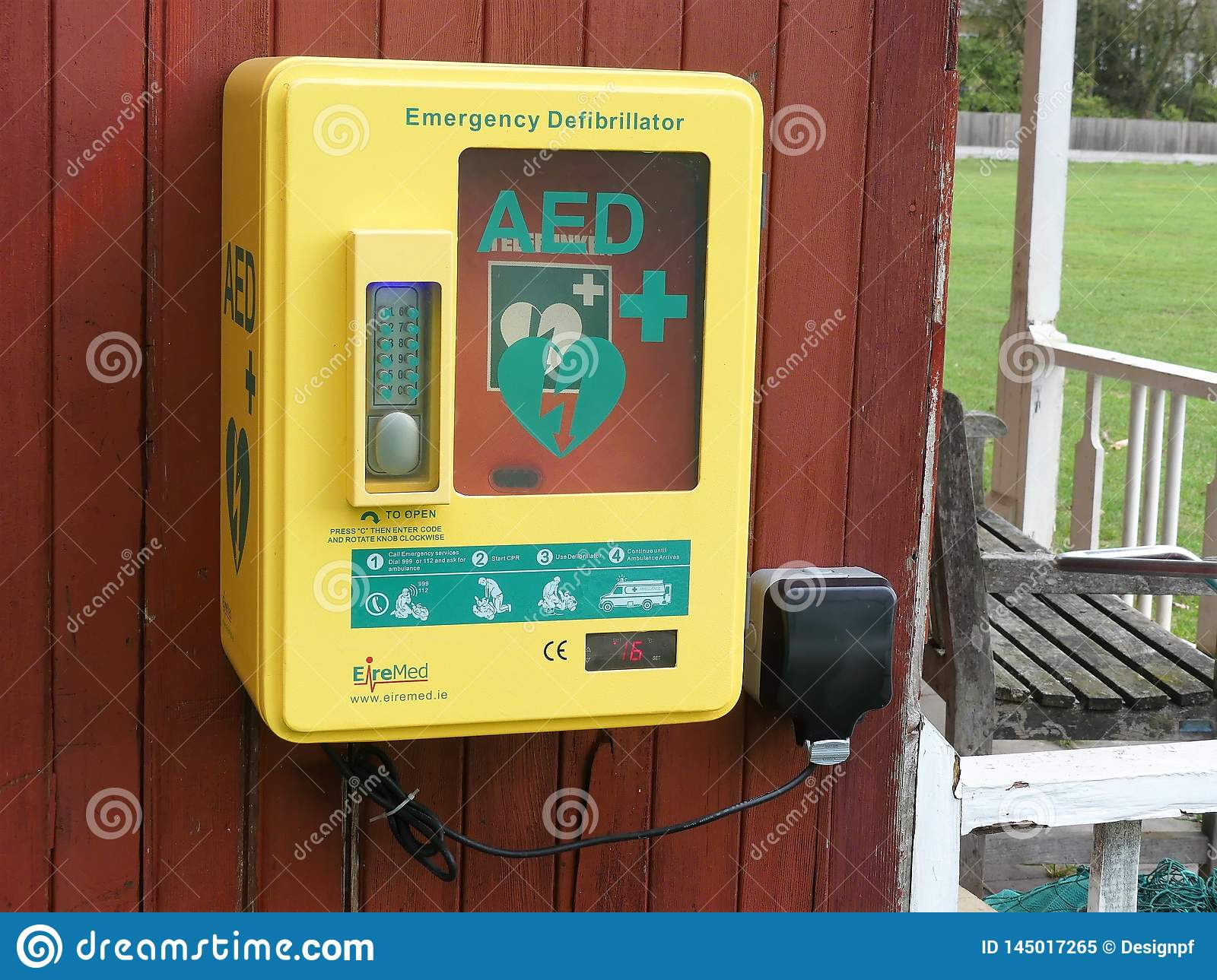 Automatic External Defibrillator AED steel unit mounted to outside wooden wall