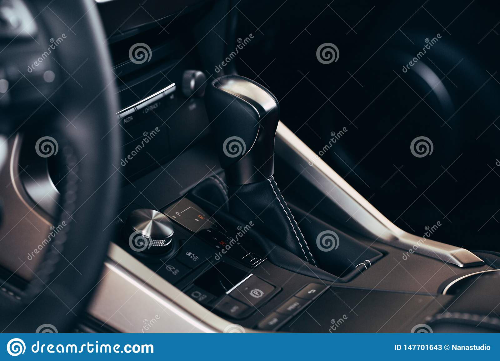 Selector automatic transmission with perforated leather in the interior of a modern expensive car. The background is blurred