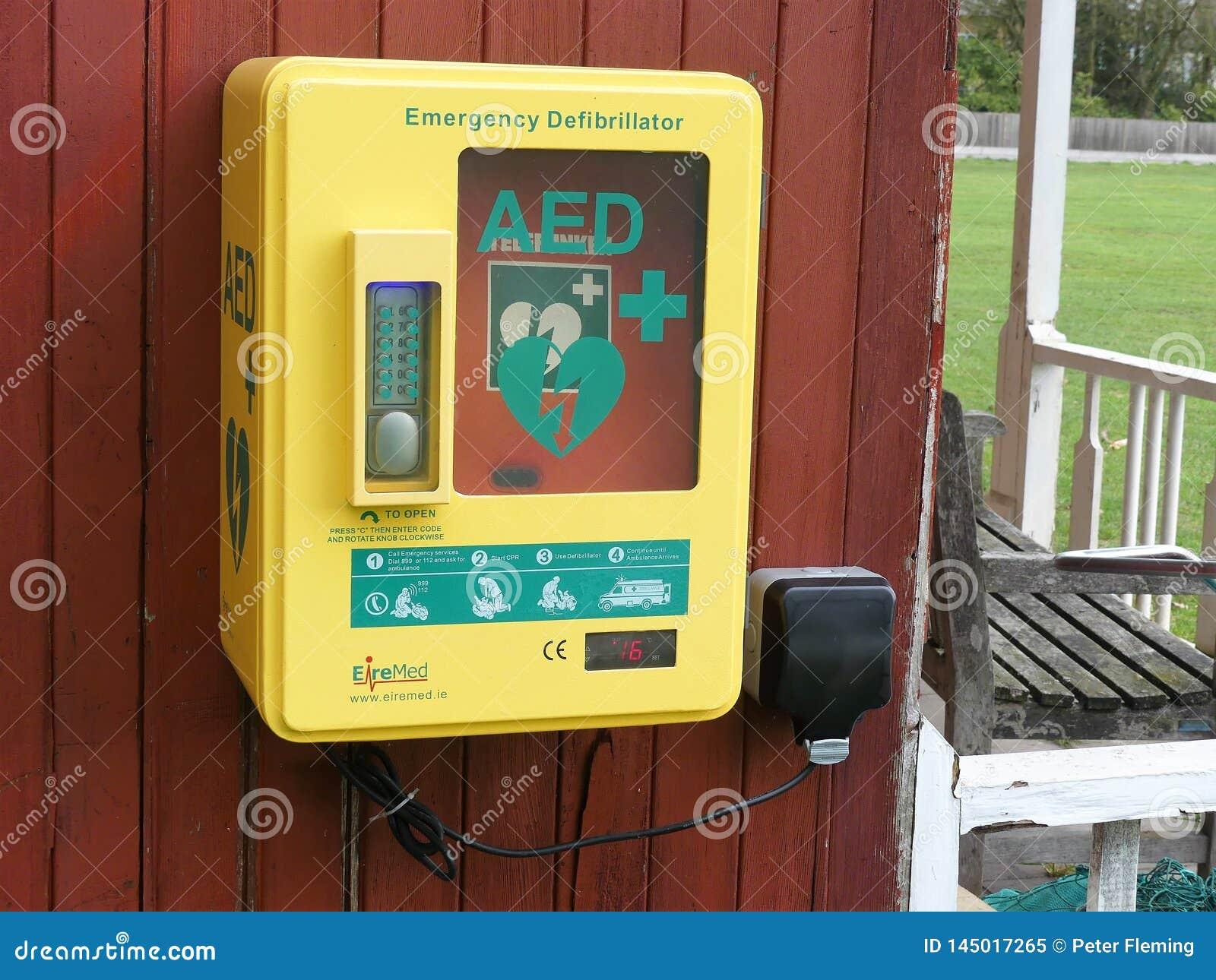 Automatische Externe Defibrillator AED-staaleenheid opgezet aan buitenkant houten muur
