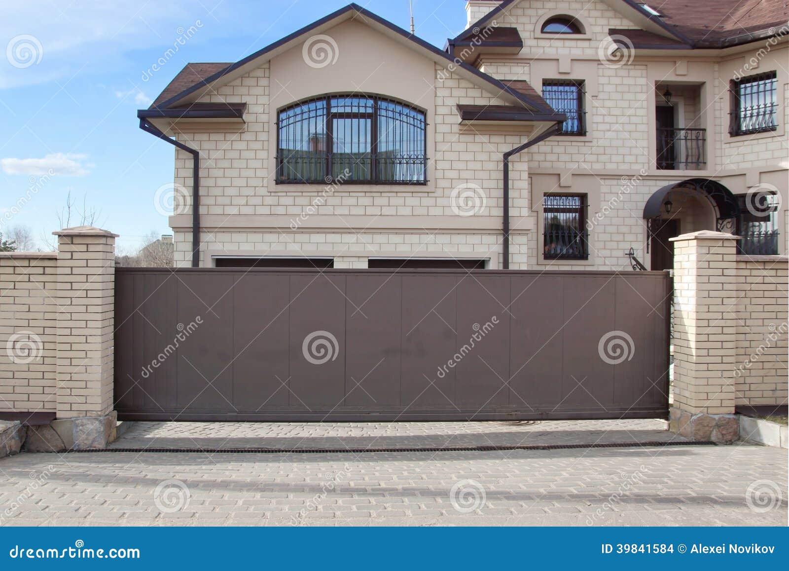 automatische poort en enig rood huis xxxl stock foto. Black Bedroom Furniture Sets. Home Design Ideas