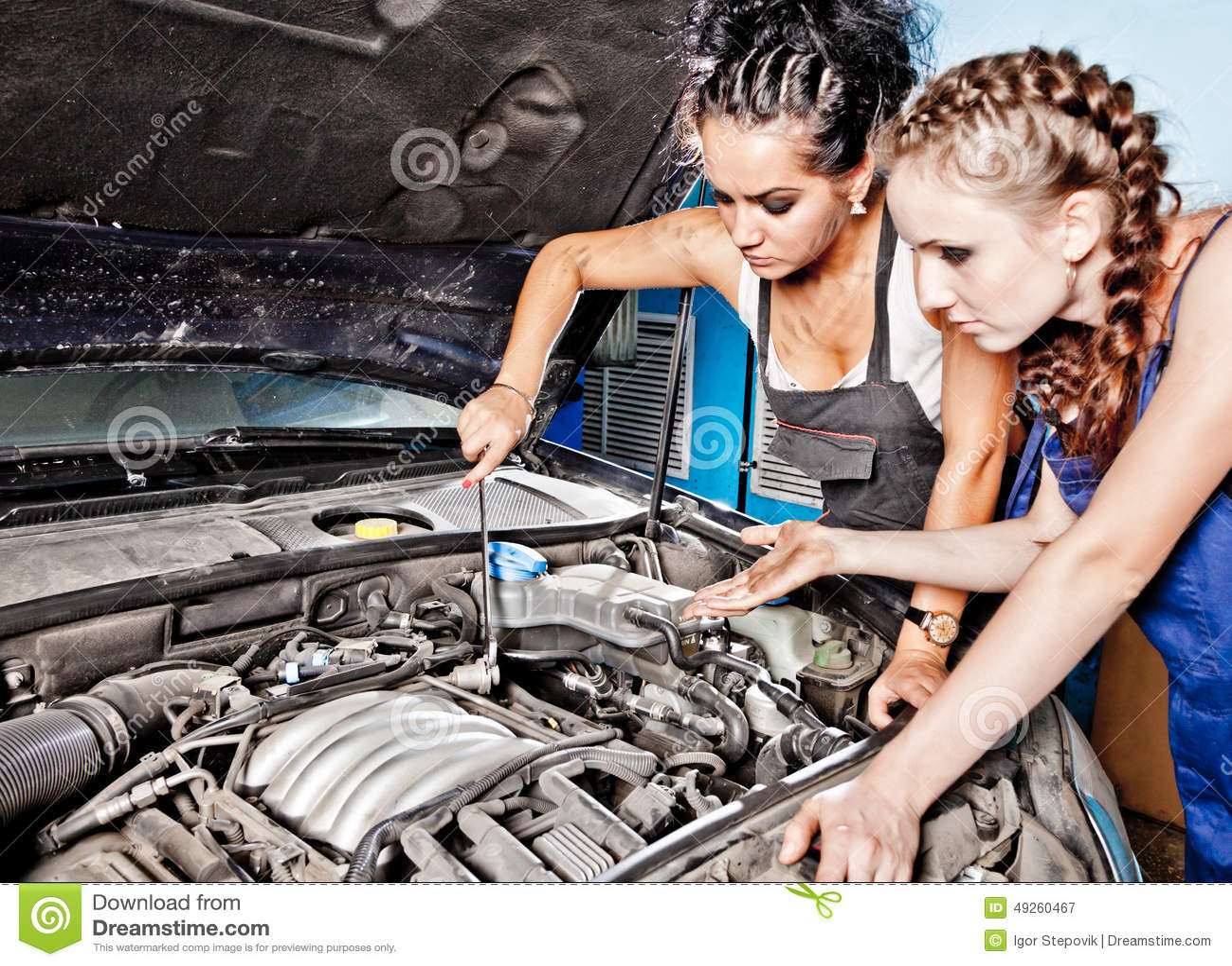 Automechaniker Mit Zwei Frauen, Der Ein Auto Repariert Stockbild ...