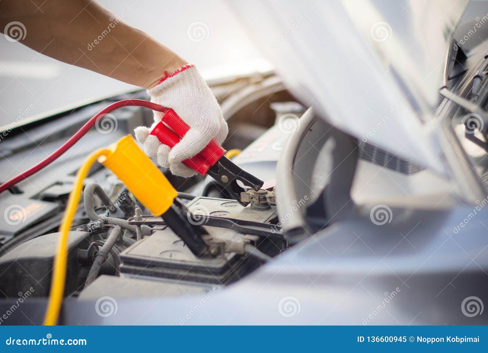 Automechanikermann unter Verwendung der Körperverletzungsstarthilfekabel, zum einer leeren Batterie aufzuladen Abschluss herauf H