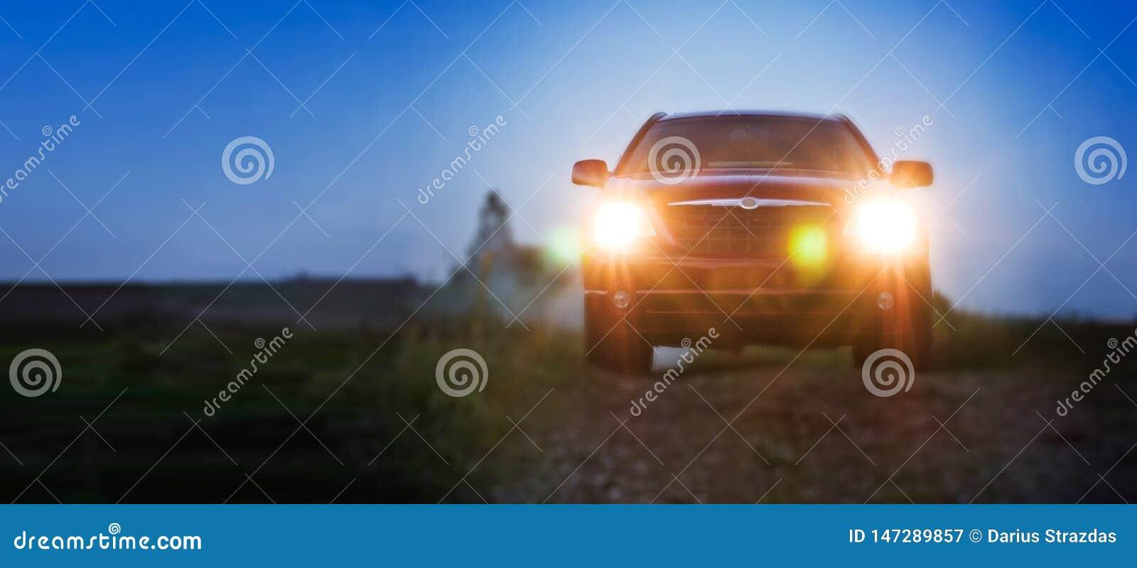 Automobile rossa molto bella alla notte con le luci sopra