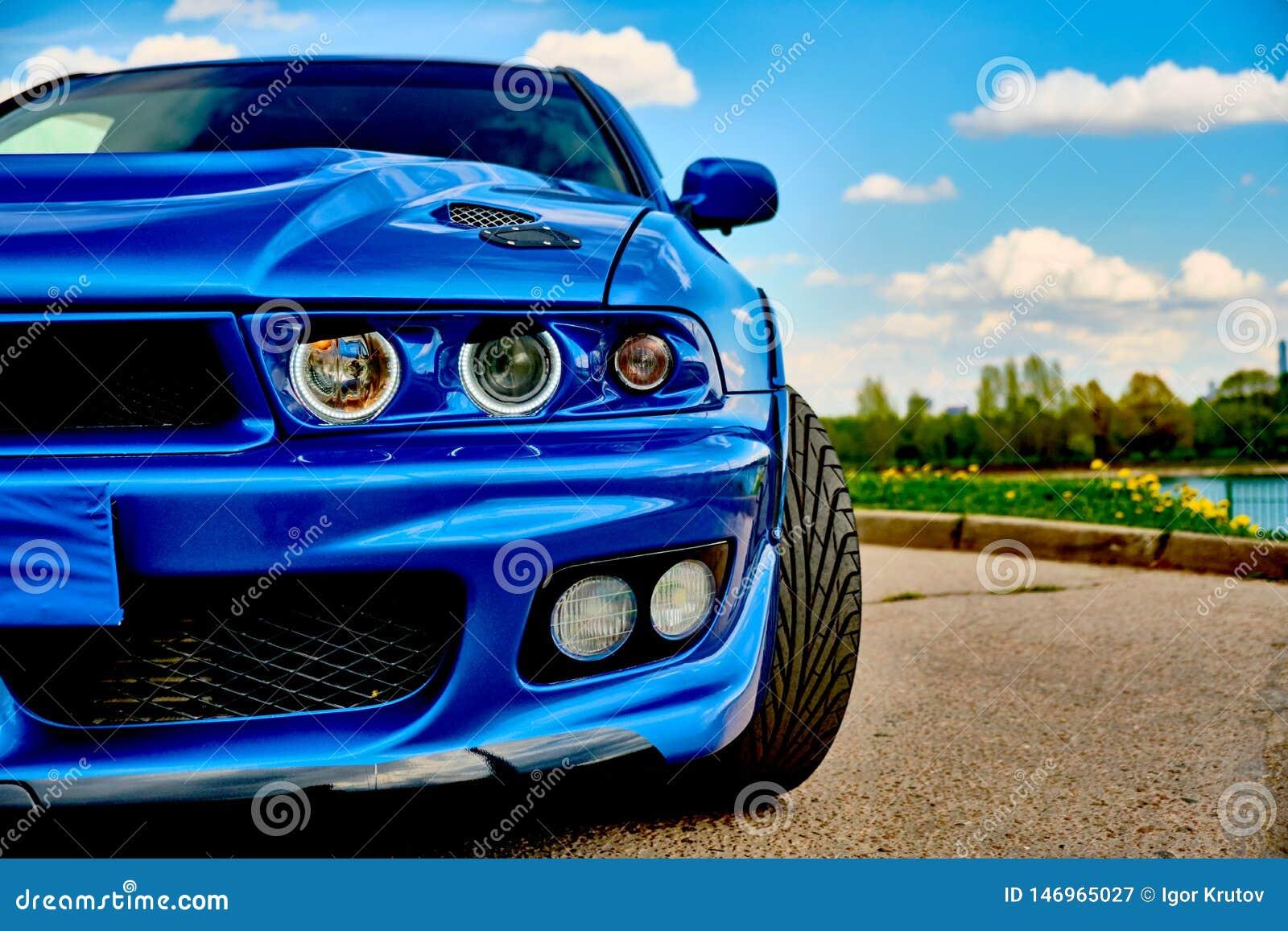 Automobile sportiva aggressiva in blu contro lo sfondo della natura