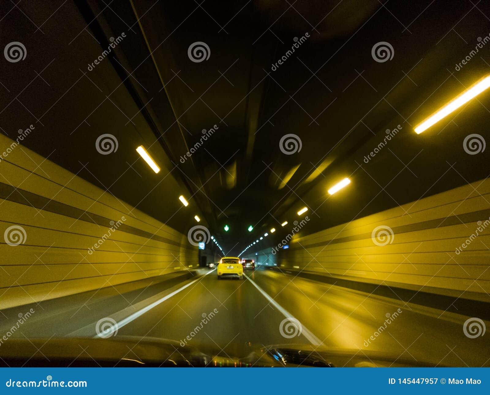 Automobili di accelerazione dentro un fondo urbano del mosso del tunnel della strada principale