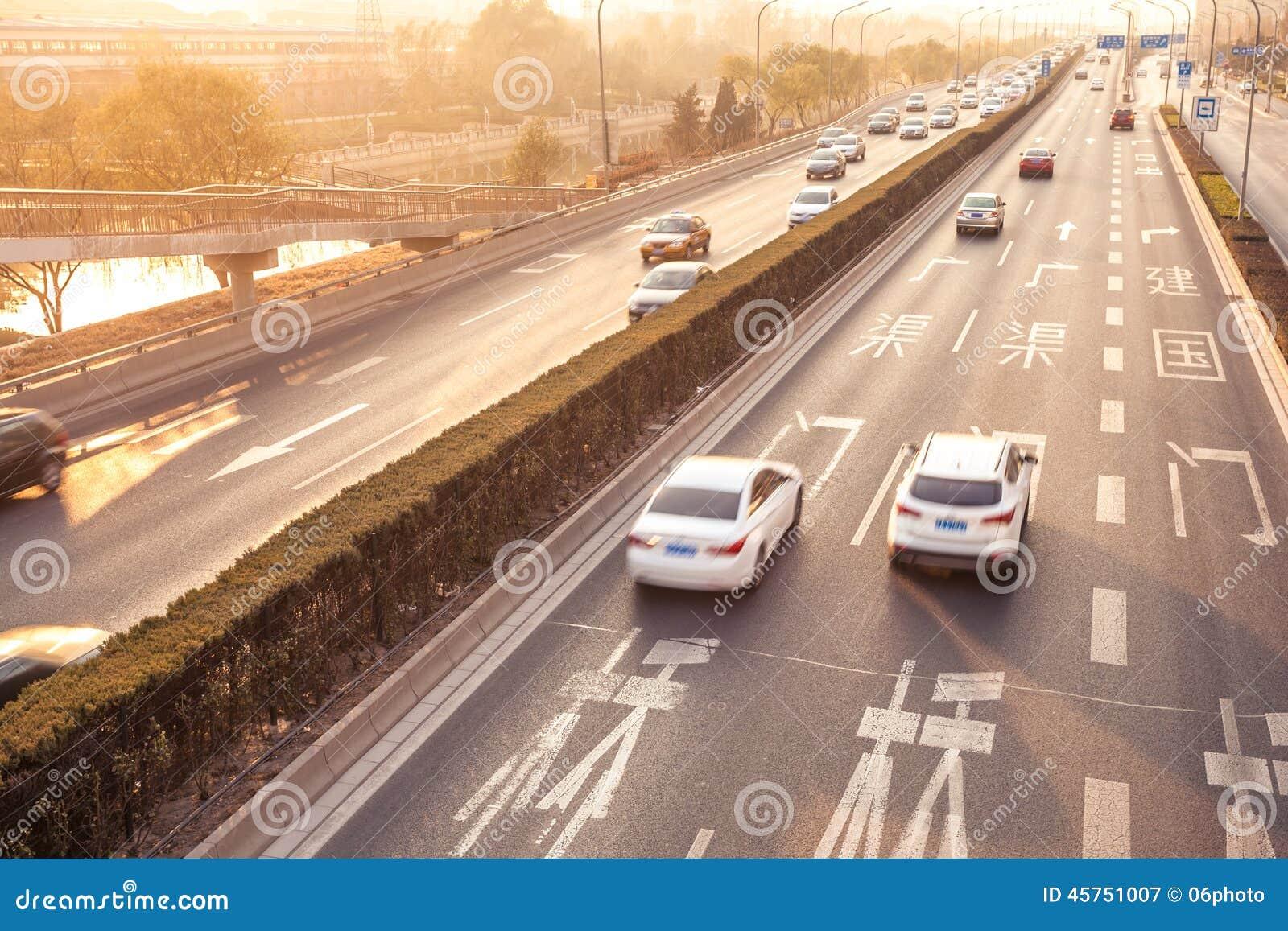 Automobili nel mosso sulla via durante il tramonto