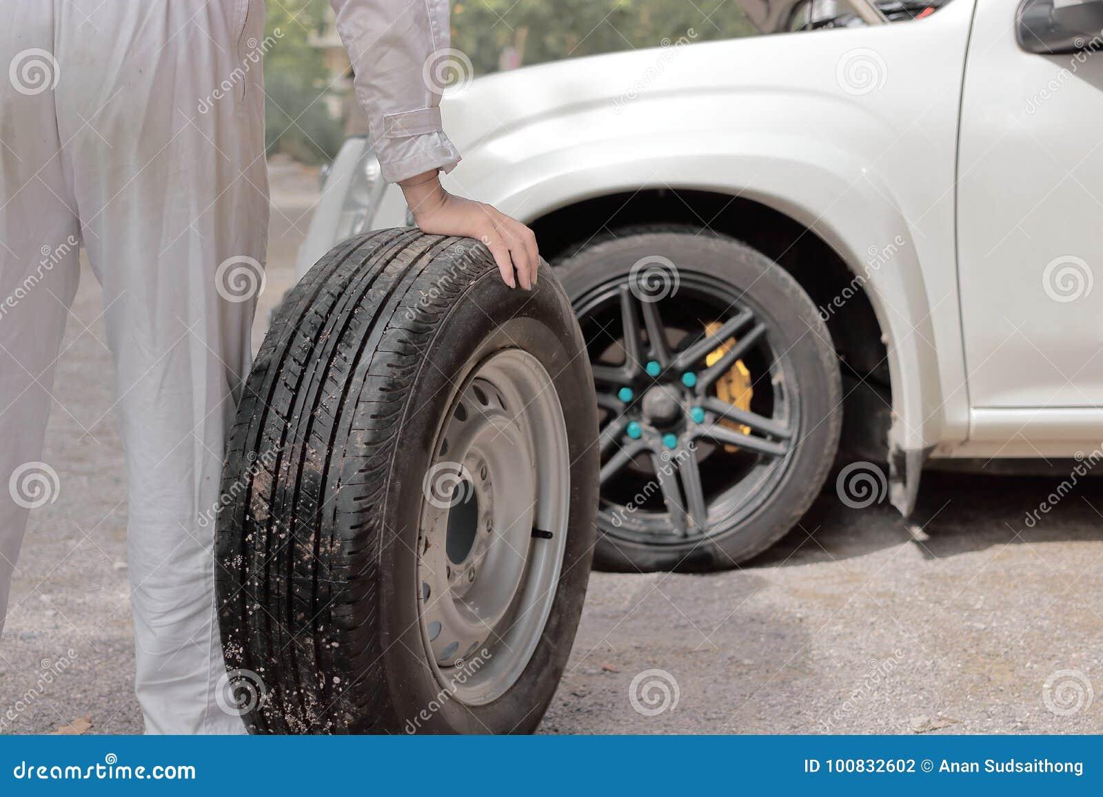 Automobilowy mechanika mężczyzna niesie dodatkowej opony narządzania zmianę koło samochód Auto remontowa usługa