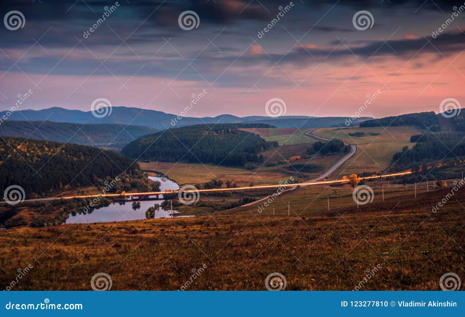 Autostrady i drogi most nad rzeką przy zmierzchu wieczór słońcem na tle góry