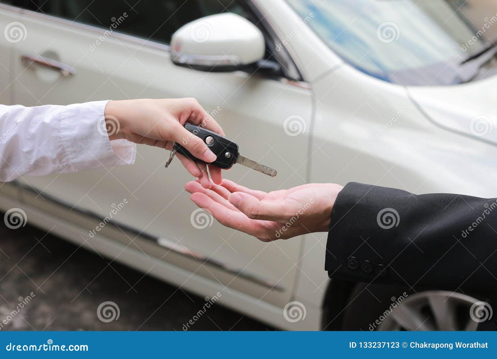 Autoverkoper die de sleutels voor een nieuwe auto overhandigen aan jonge zakenman