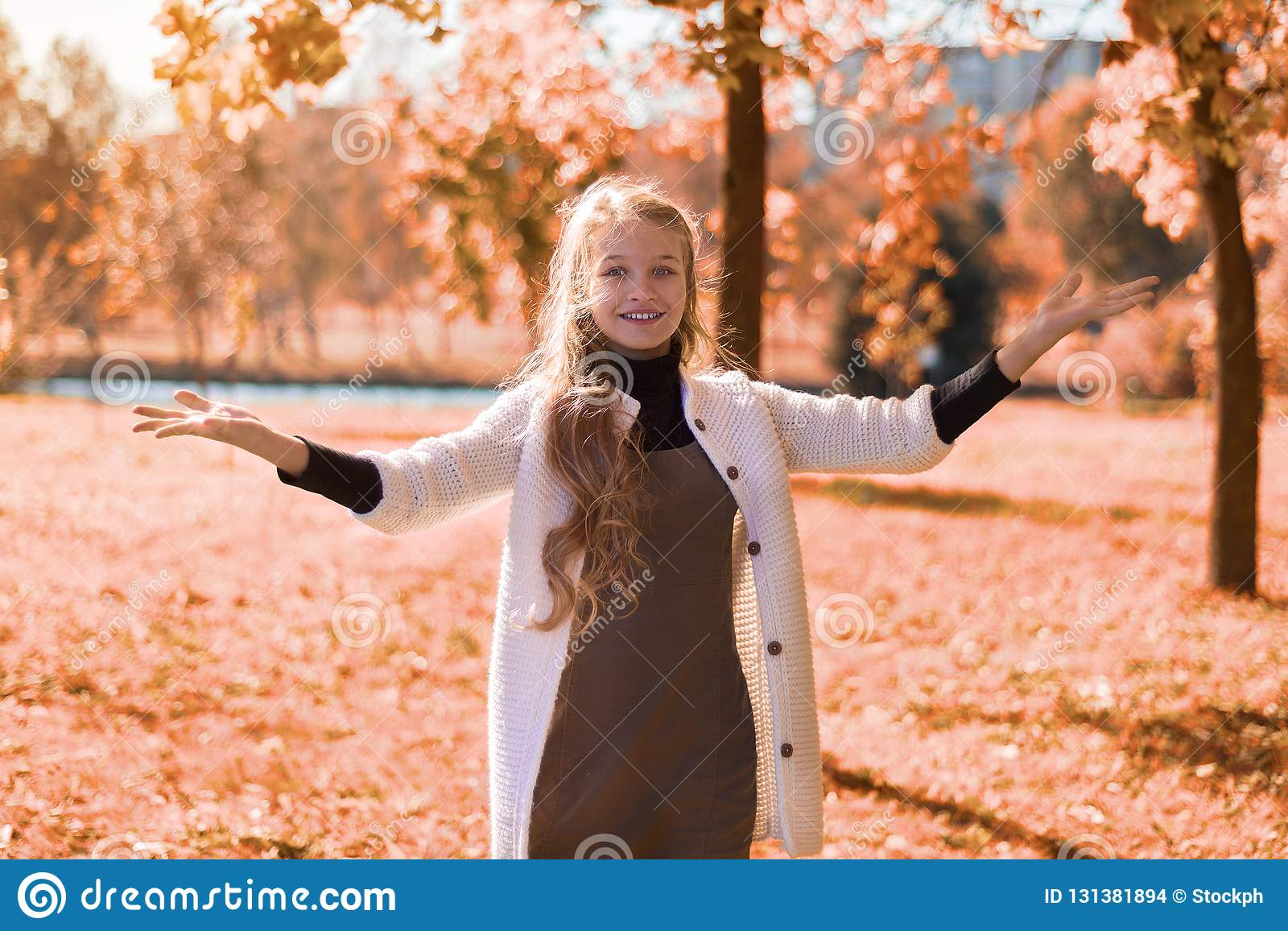 Autumn beautiful portrait of a young girl in the park with foliage. teenager smiles and hands up