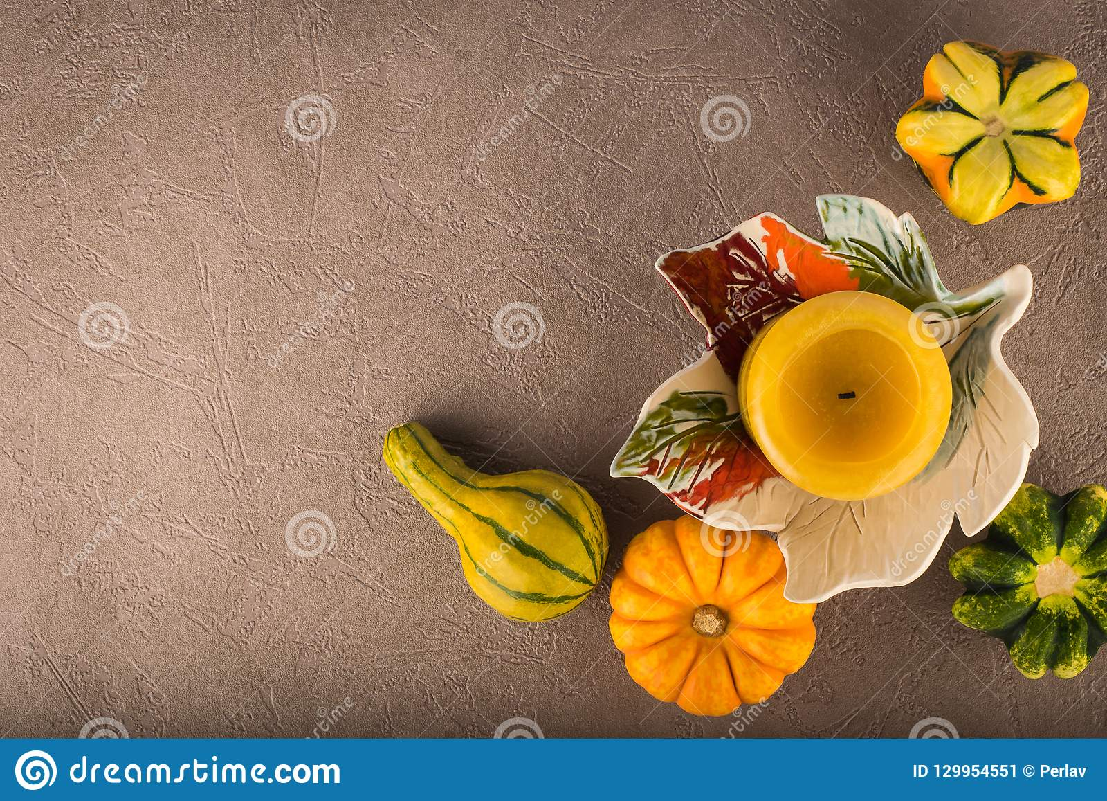 Autumn composition of decorative pumpkins and candle