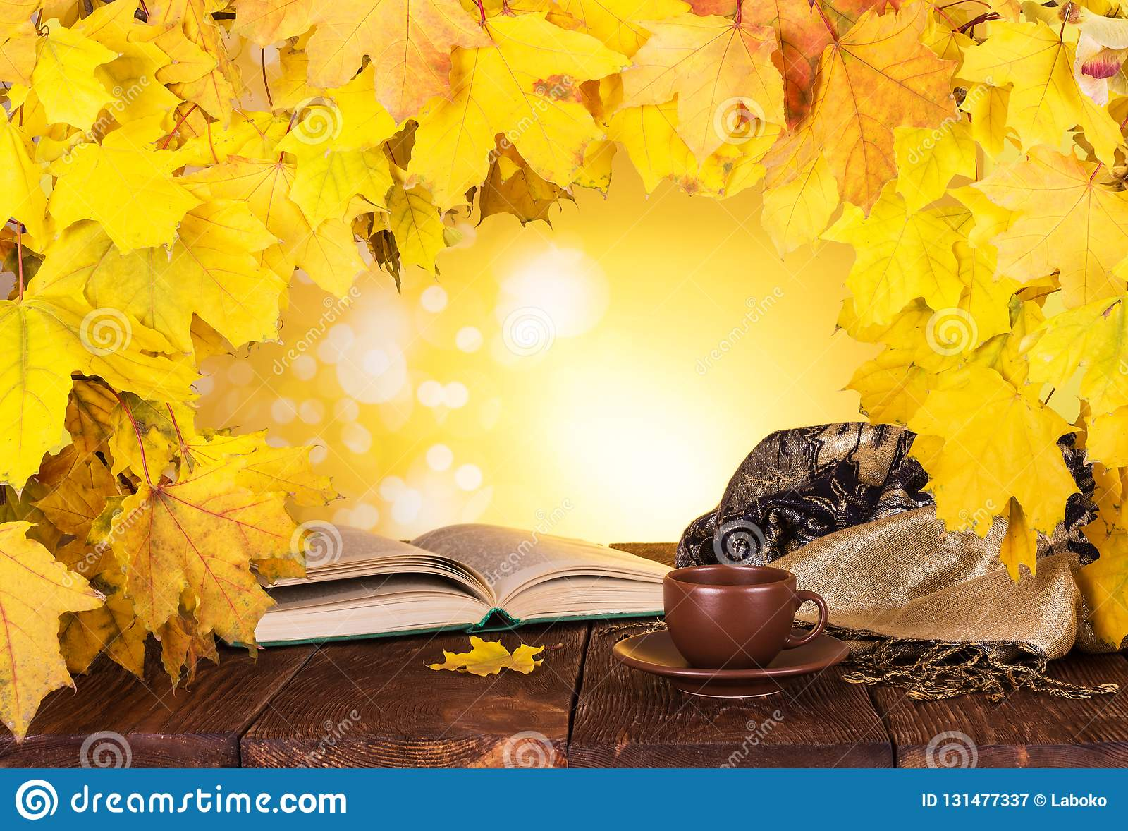 Autumn composition. Maple leaves, hot tea and open book