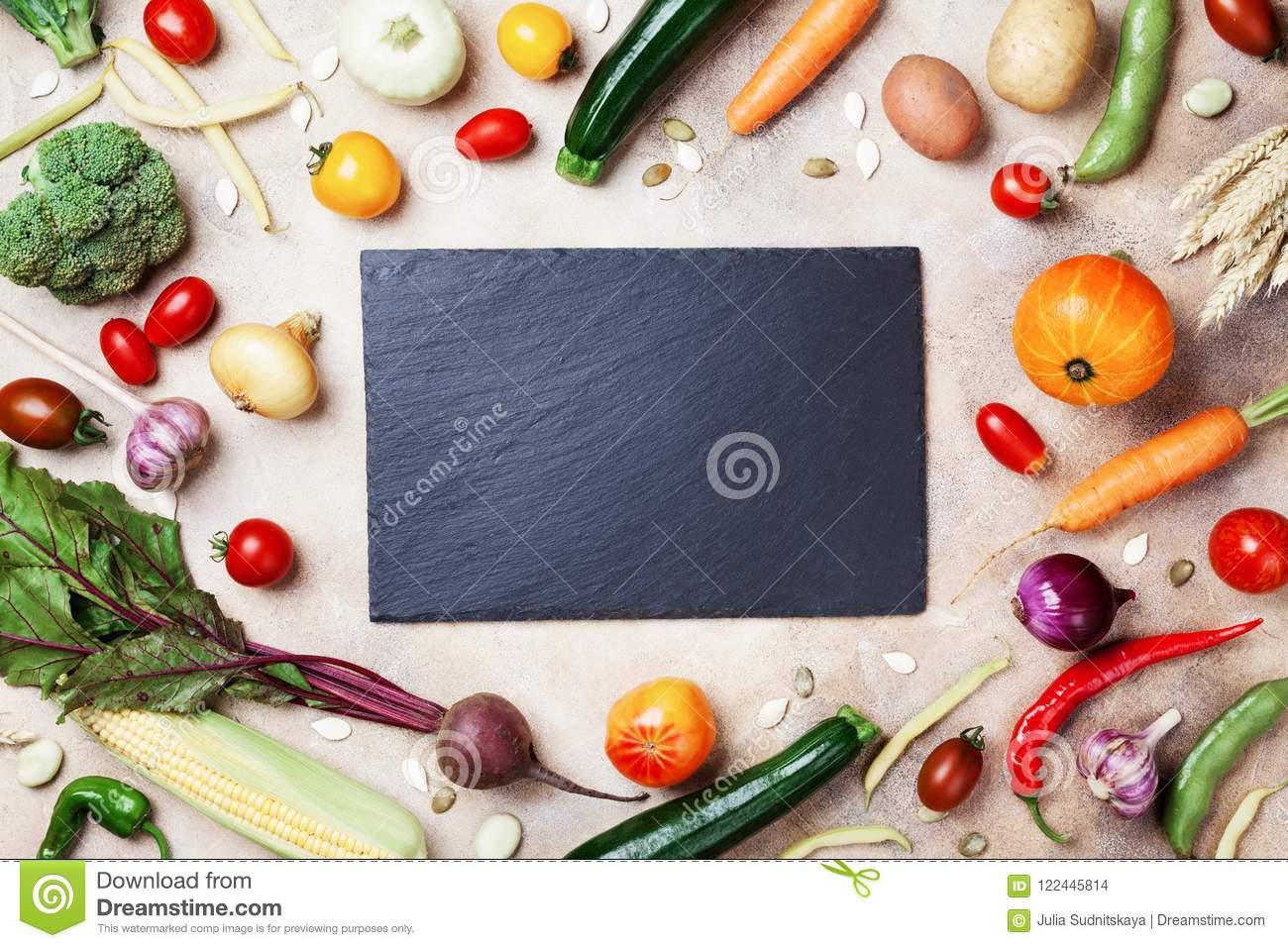 Autumn farm vegetables, root crops and slate cutting board top view with copy space for menu or recipe. Healthy and organic food.